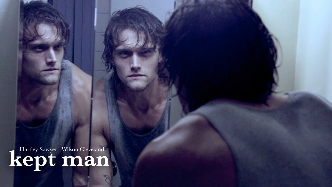 Hartley Sawyer as Brian in Kept Man staring at his reflection in the mirror.