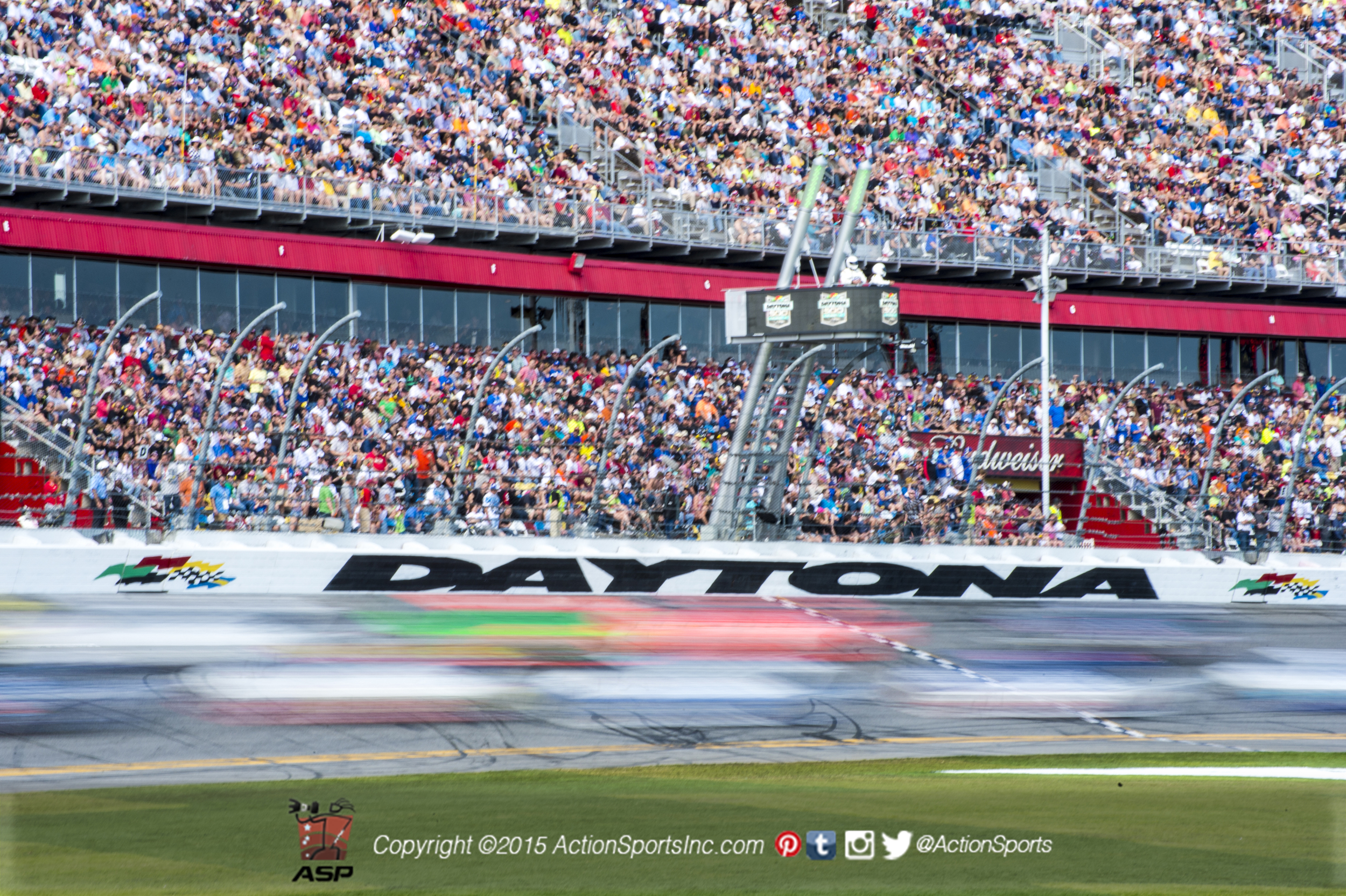 Stock cars race down the front straight of the Daytona International Speedway in a blur during the Daytona 500