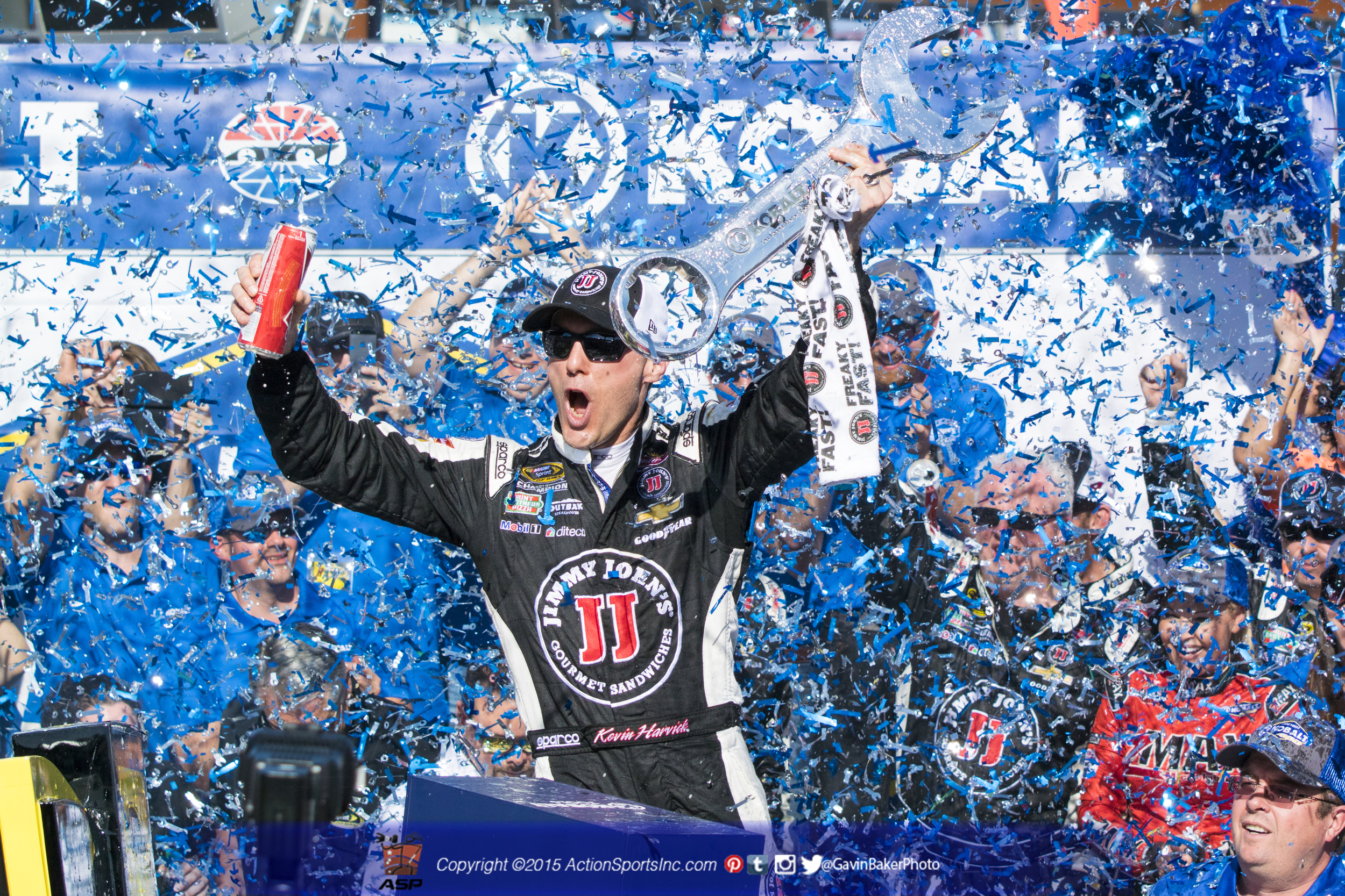 Kevin Harick (4) celebrates his win in victory lane holding his trophy above his head while confetti rains down around him.