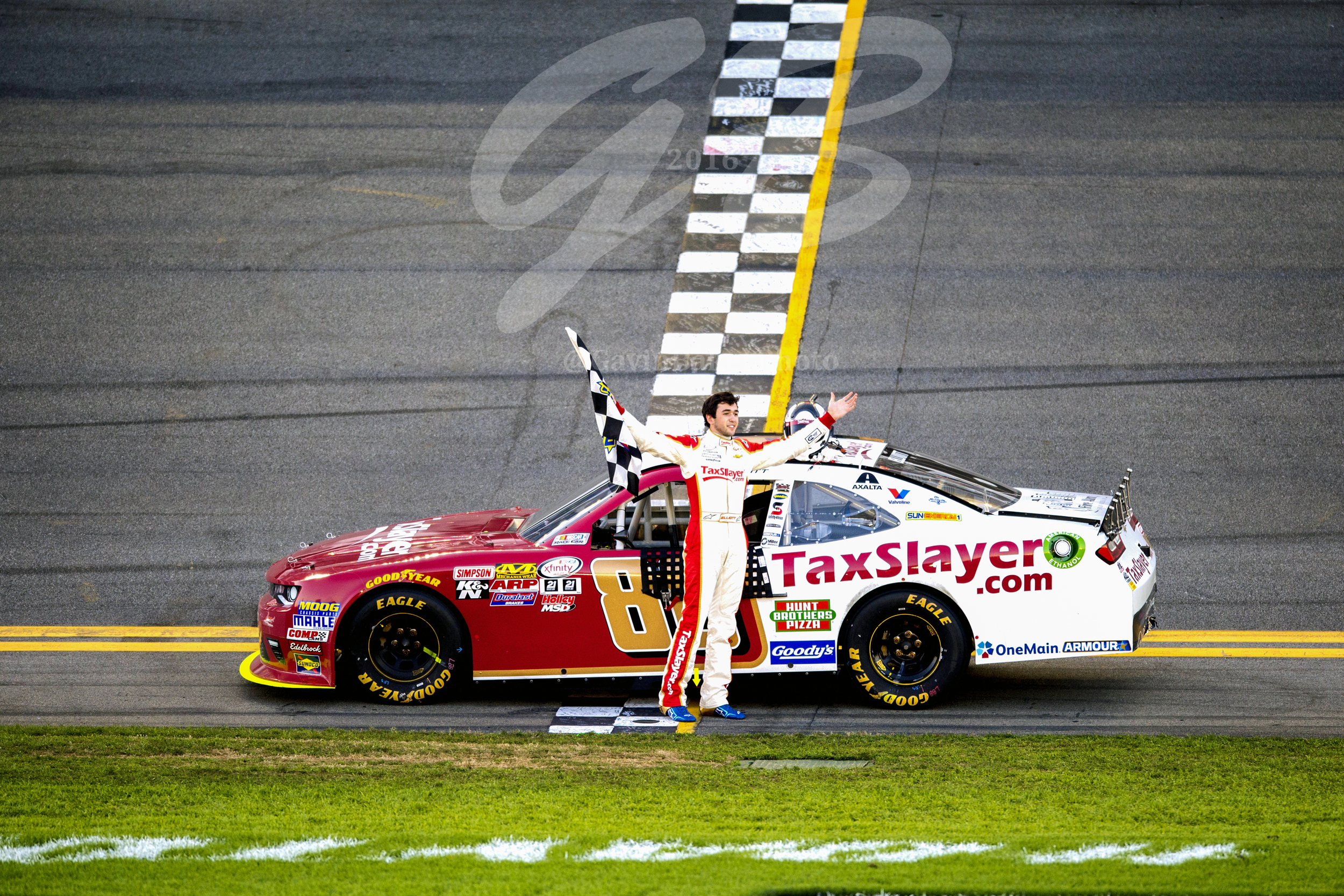 Chase Elliott stands in front of the TaxSlayer.com Chevy on the start / finish line celebrating his victory in the Xfinity race. Chase's race car had run out of fuel and had to be pushed back to Victory Lane.