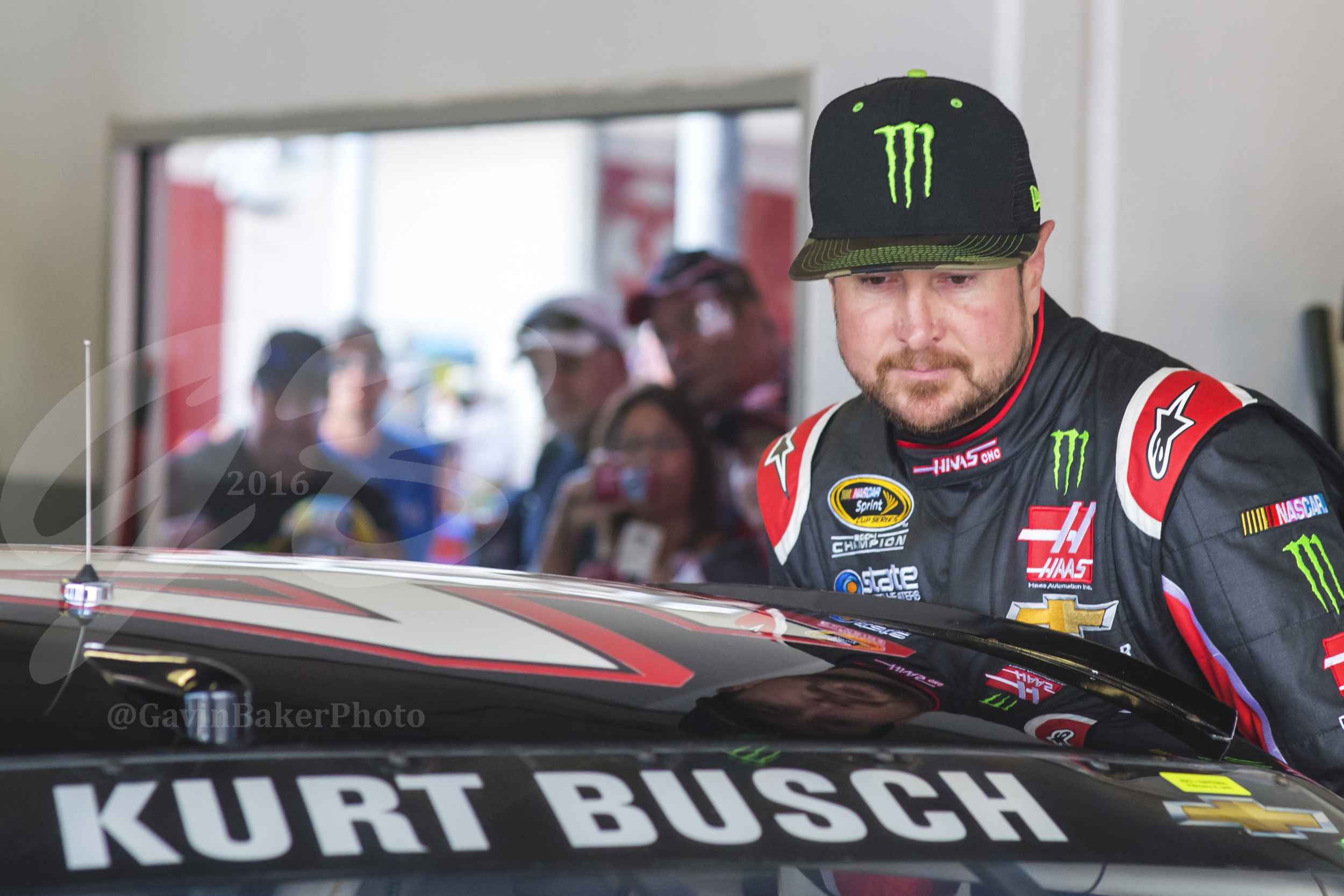 Fans look on and snap pictures from behind the viewing area of the garage as Kurt Busch climbs into his racecar