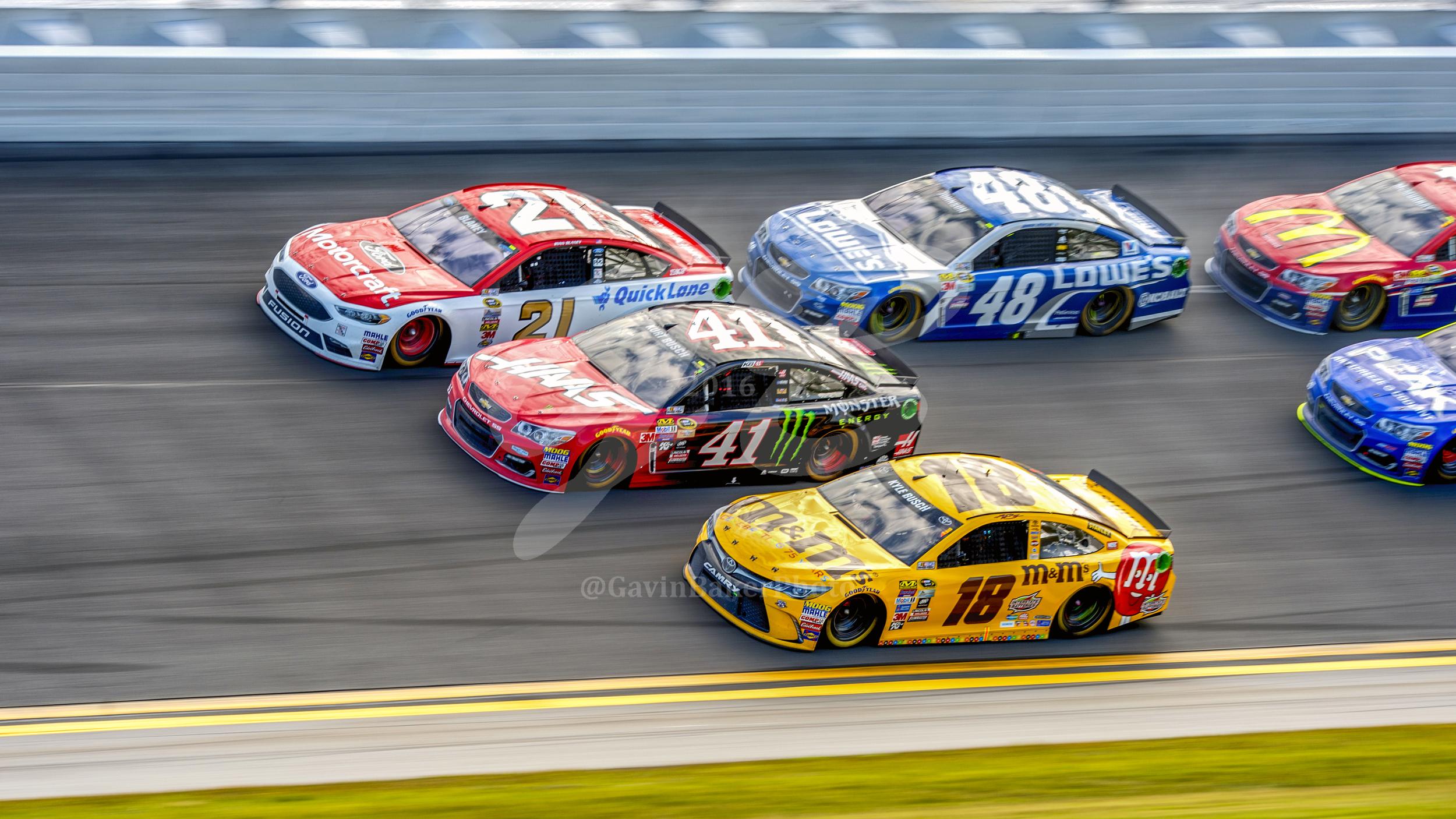 Kurt Busch, Kyle Busch, Ryan Blaney, and Jimmie Johnson lead the pack through turn one of the Daytona 500.