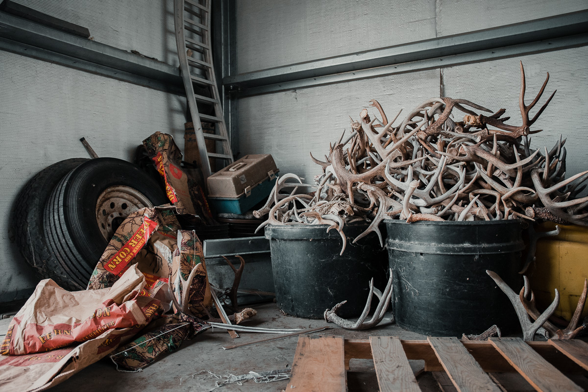 two large buckets of deer antlers in the corner of a garage