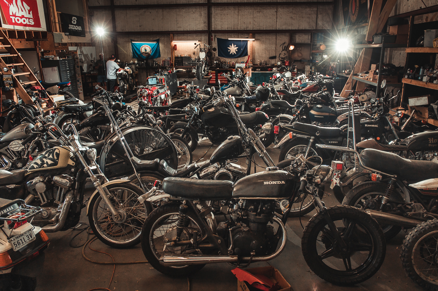 Large variety of vintage motorcycles waiting for mechanical work in an automotive shop