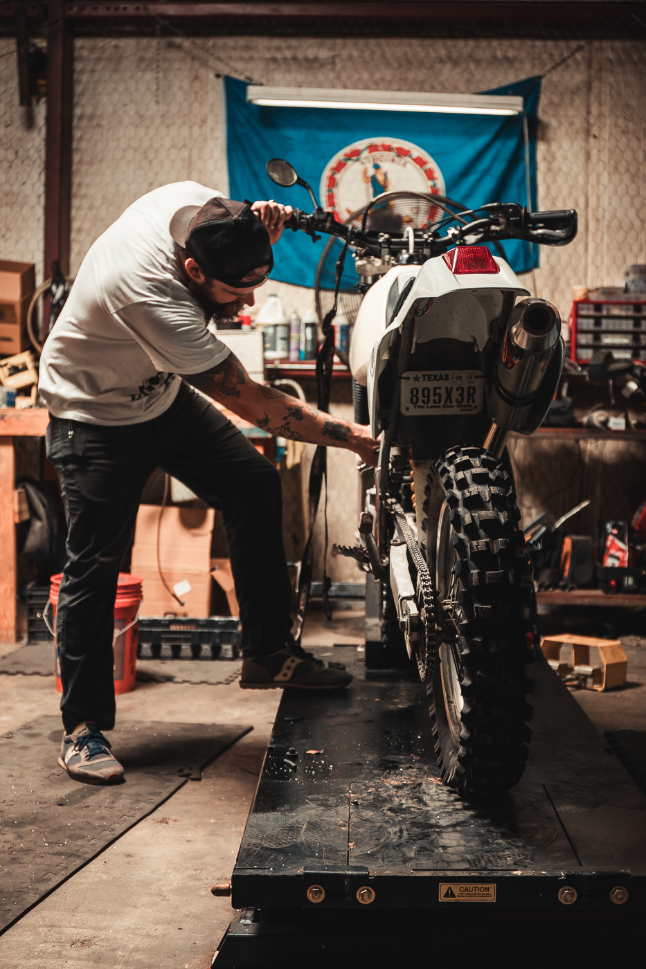 motorcycle mechanic making adjustments to a dirt bike in his automotive shop