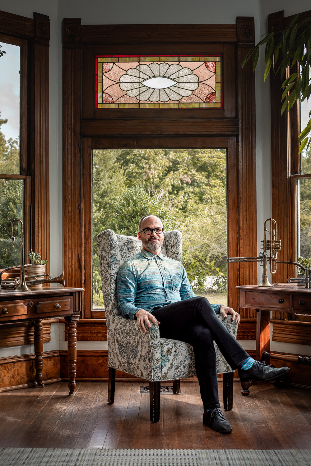 portrait of well dressed musician sitting in paisley chair in vintage living room
