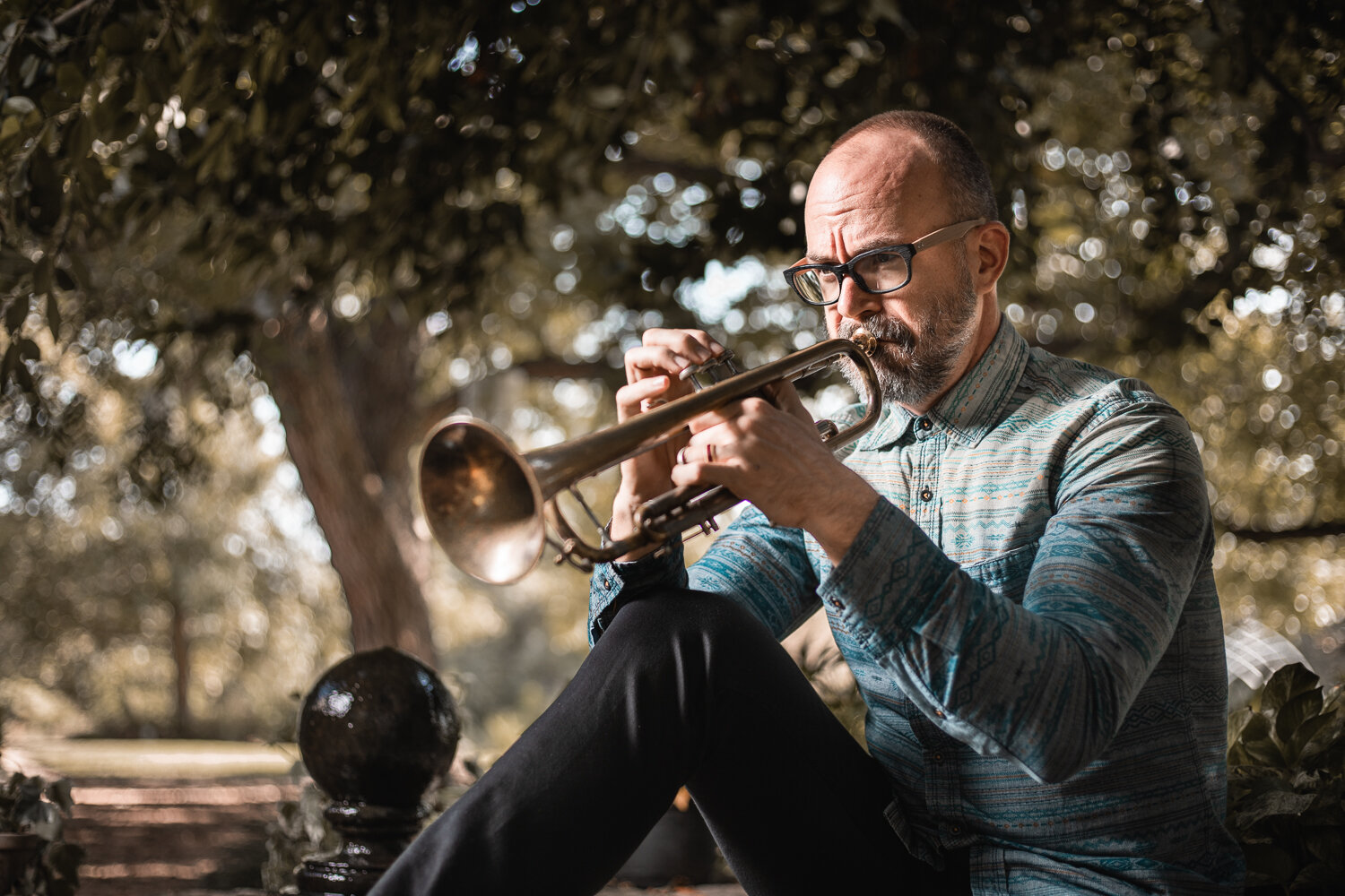 outdoor portrait of well dressed musician playing trumpet in a garden under the shade of a large tree