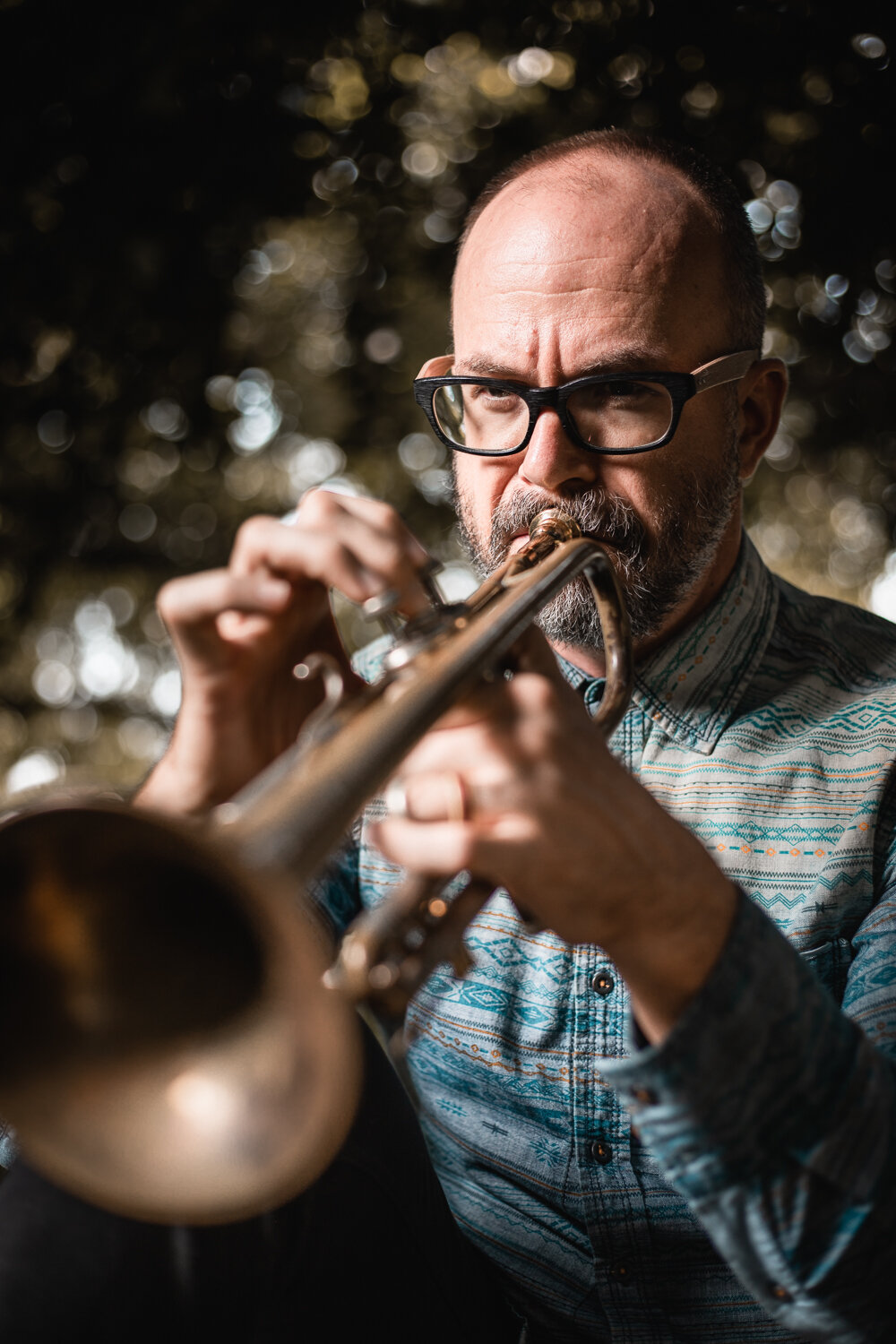 outdoor portrait of well dressed musician playing trumpet in a garden