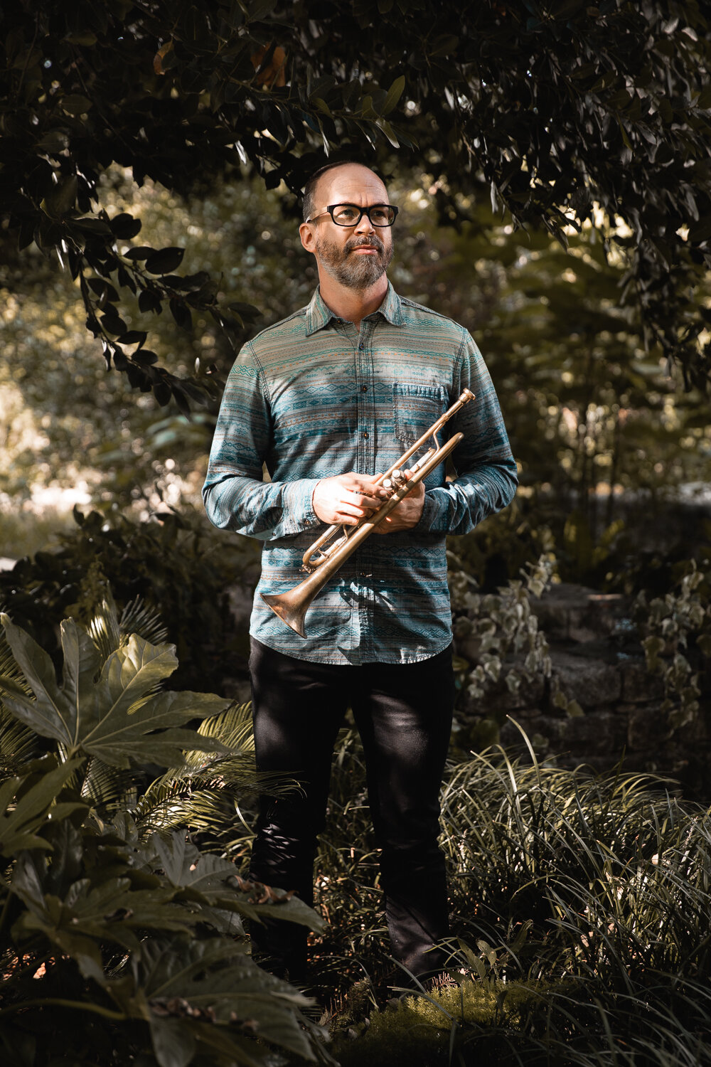 outdoor portrait of well dressed musician holding trumpet in a garden