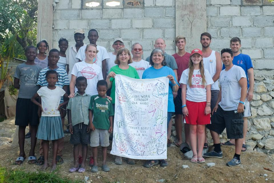 """The Marion Methodist team with the church they built, the Pastor & his family. The banner says """"God's work through our hands"""" in English & Creole. There are two identical banners, one went home to Marion the other will hang in the church they built."""