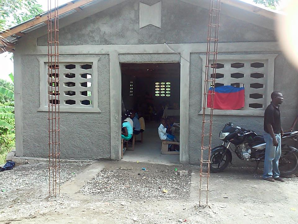 """An """"After"""" picture. Besides the rebar sticking of of the ground, not much is the same. You can see the school children just inside the door. You gave them a place to learn."""
