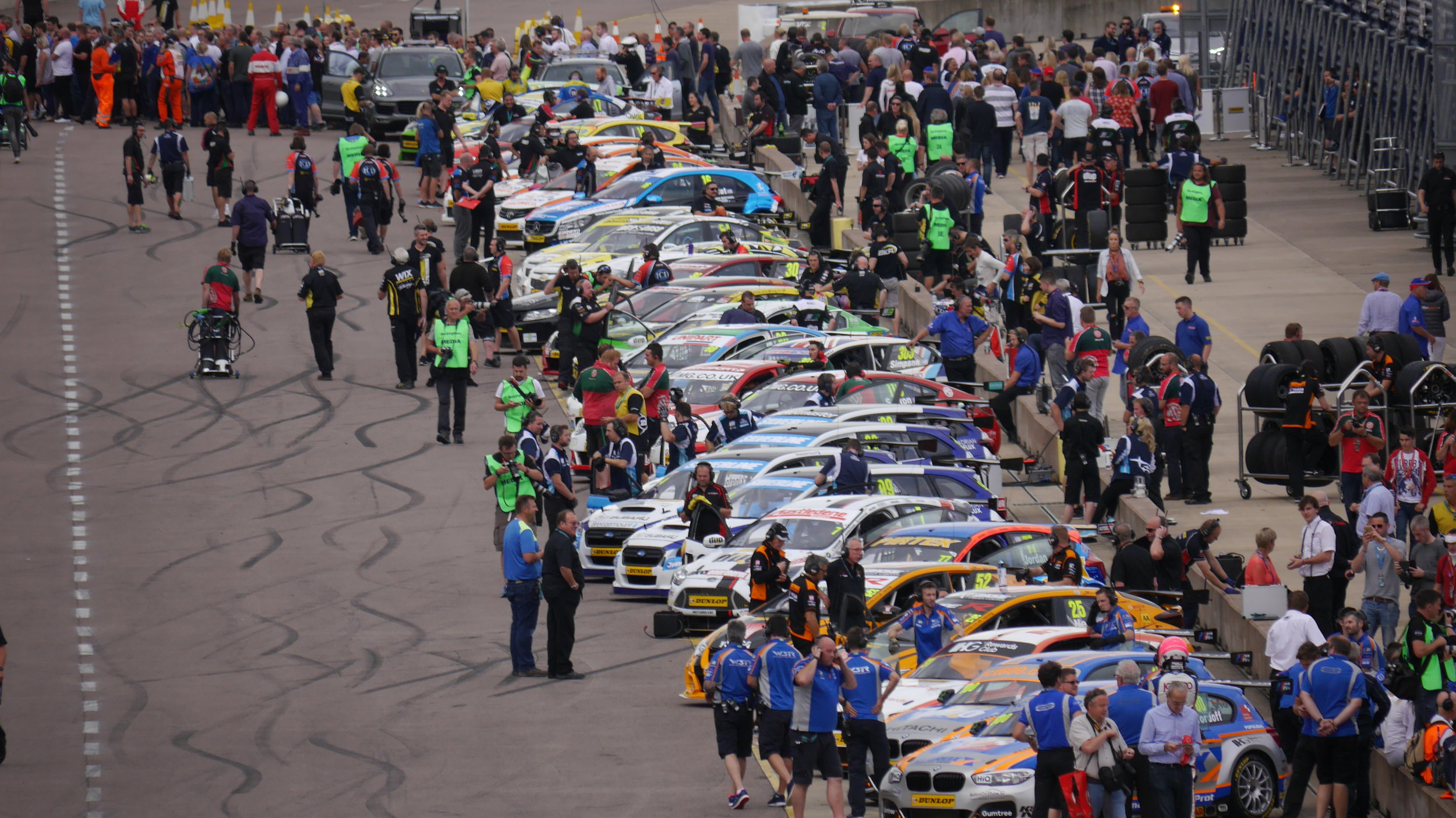 Cars and drivers assemble int he pits before lining up on the grid