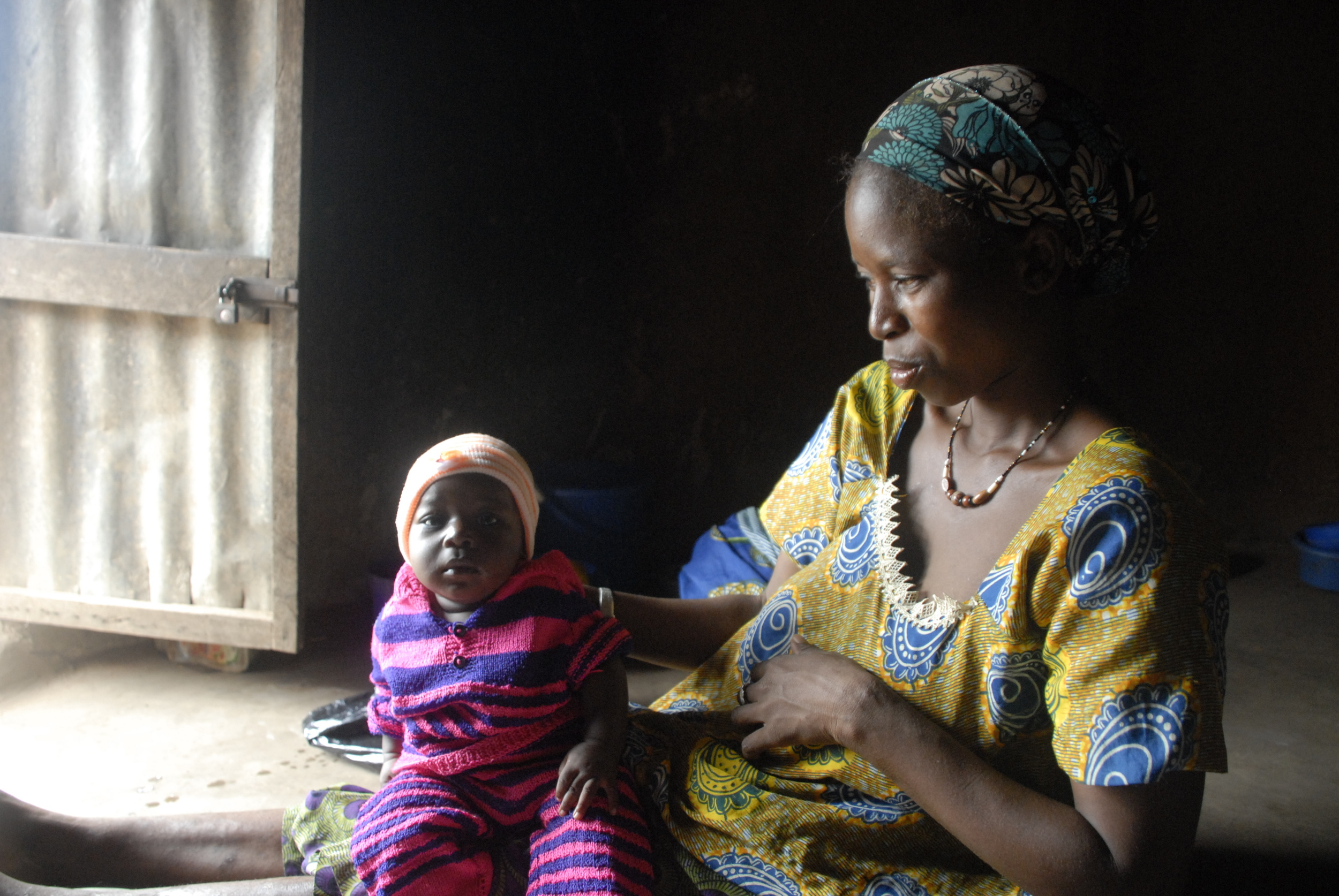 Maimouna shows off her two-month-old son's new hat in her home in northern Togo.