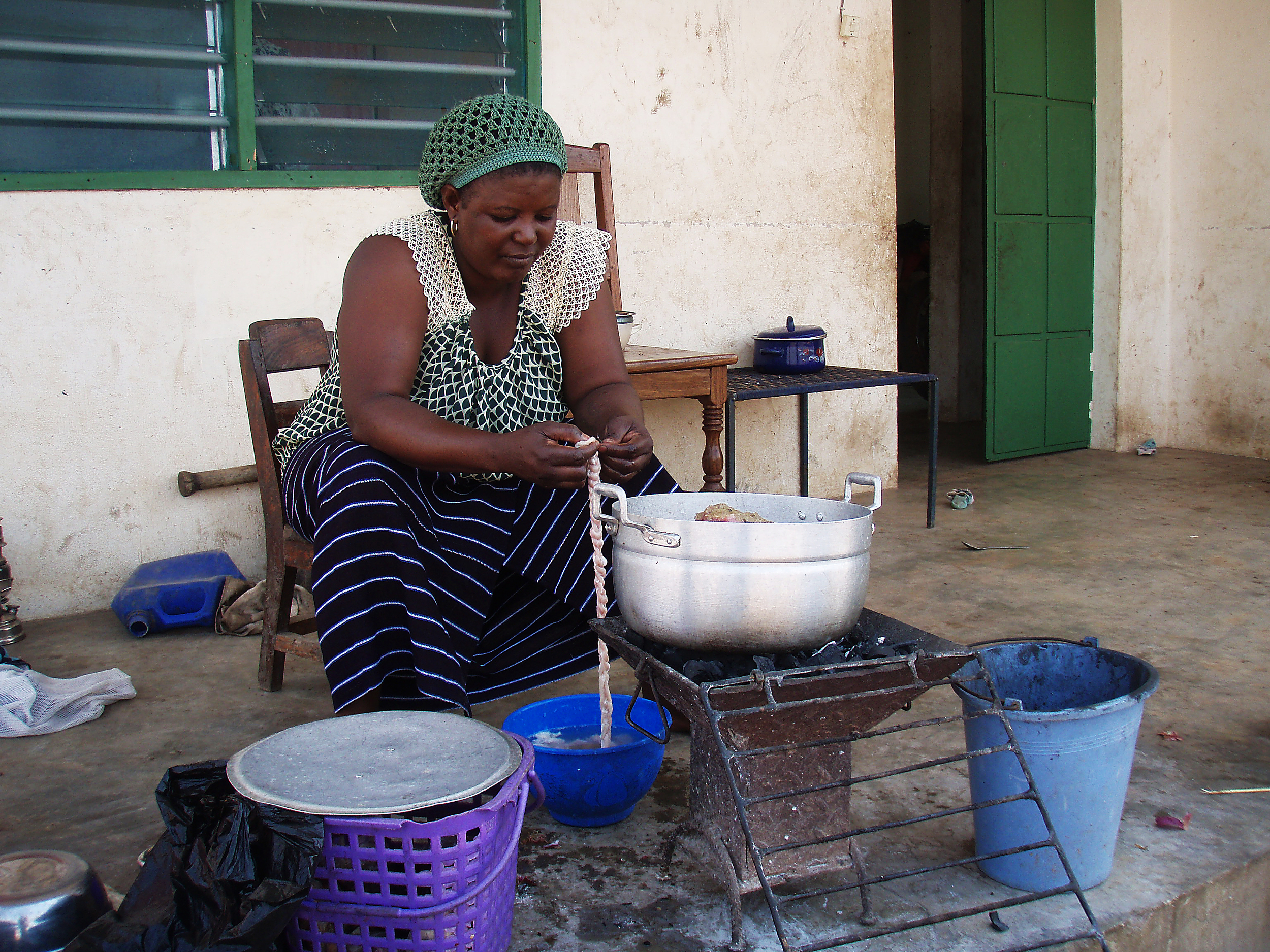 """Falilah, one of the village nurse's two wives, makes sausage from a sheep's intestines. On Tabaski, or Eid al-Adha (or the """"Festival of Sheep"""" in Togo), families slaughter a sheep to commemorate Abraham's willingness to sacrifice his son Isaac to God. God instead provided a ram for the sacrifice."""