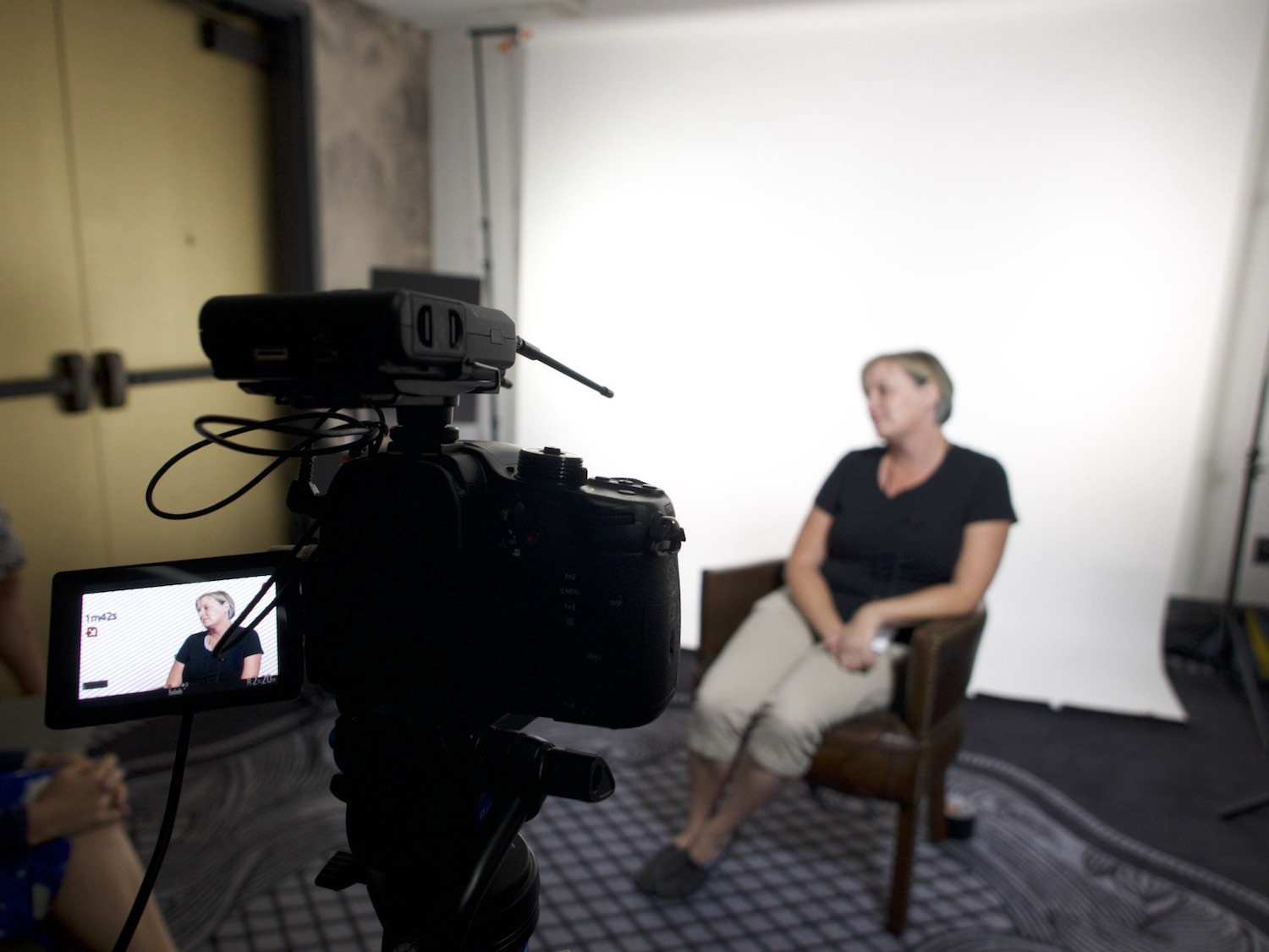 Behind the scenes interview of a woman on a white seamless backdrop focus on camera (Lumix GH4)