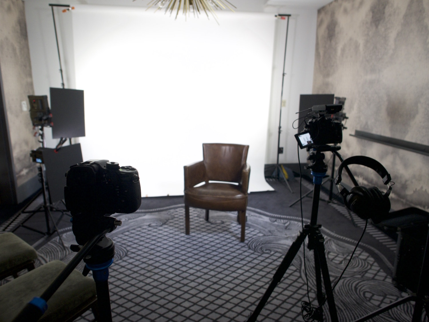 Behind the scenes interview setup on a white seamless backdrop