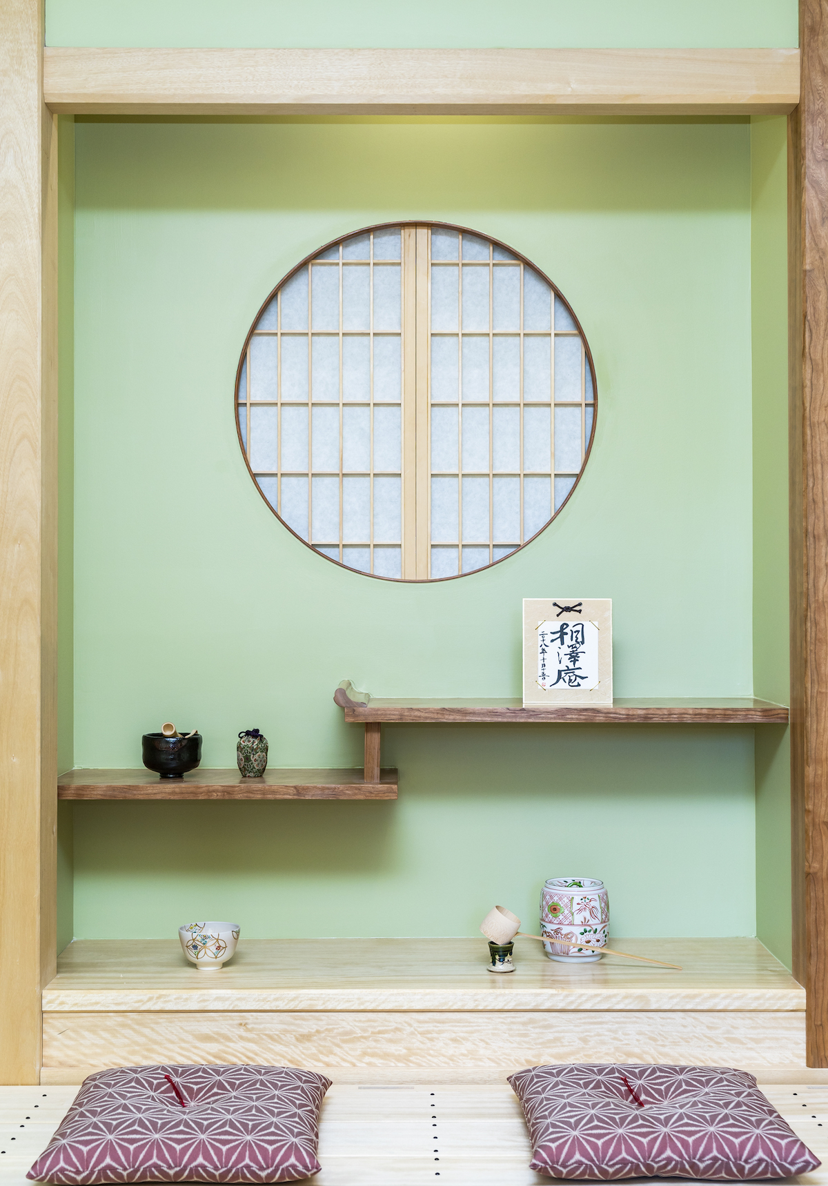 In the  chigai-dana , and floor below are placed some of the Department's prized objects for use in the Tea Ceremony. The light-colored wood is avodire, while the shelves and  toko-bashira  are American Black Cherry. the shōji in the round window are constructed from Japanese Cypress.