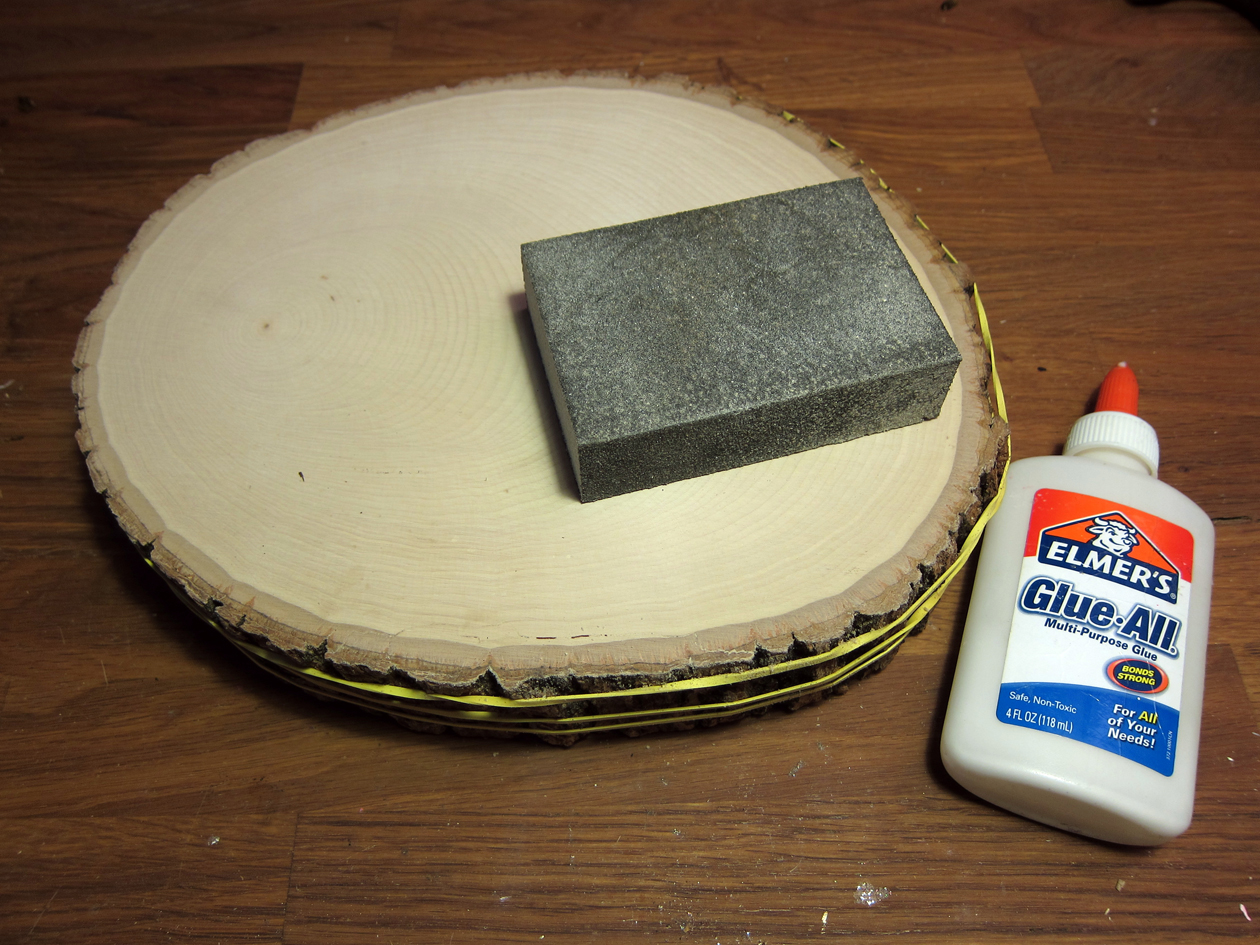 Clean surfaces by removing all dust and wood shavings. Use a wood glue to affix the bark edge back to the basswood round. Rubber-bands will help hold the piece in place as it dries. Sand front of basswood round with a fine grit sand paper.