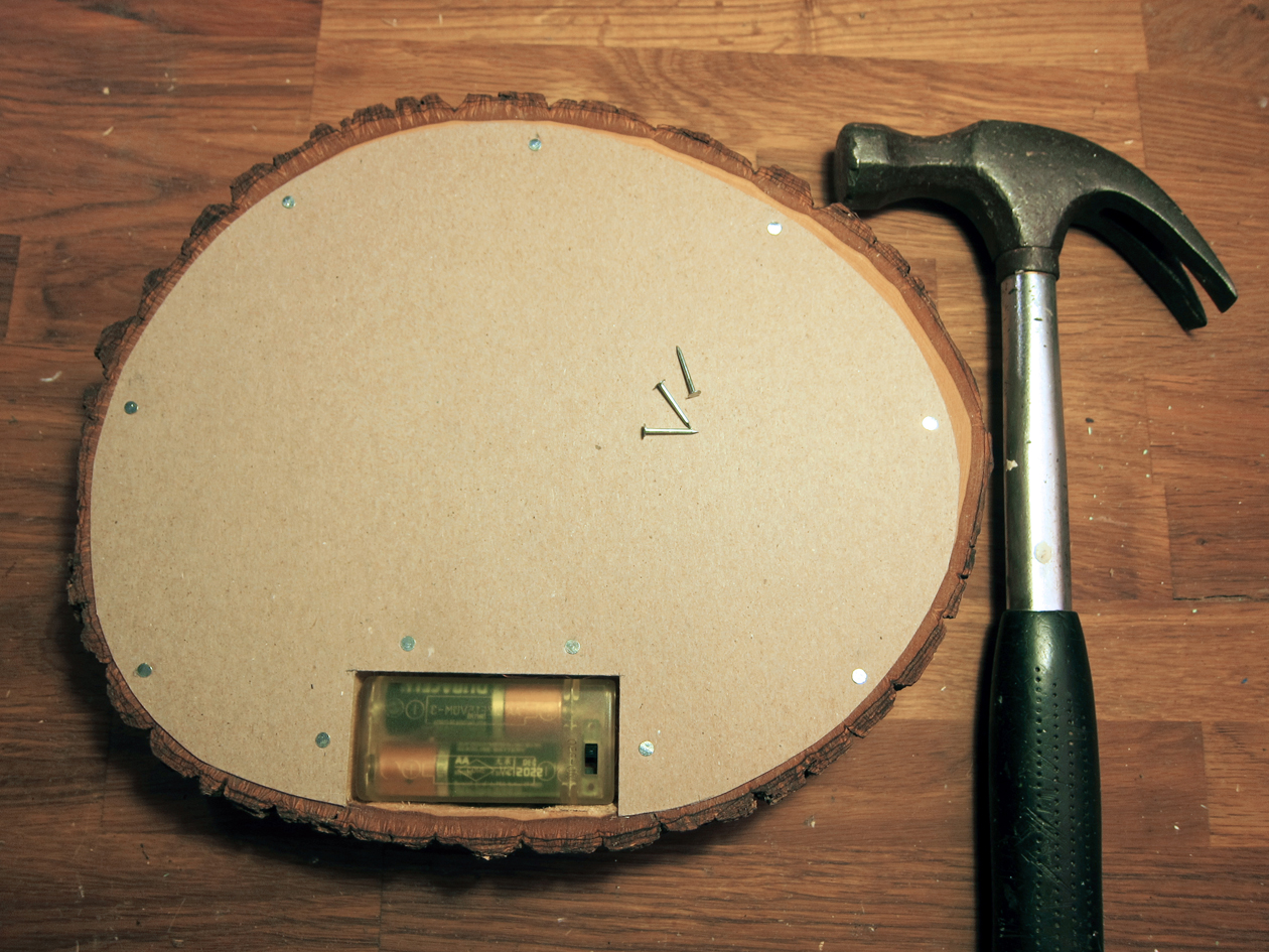 Cut a piece of chipboard to fit the back of basswood round. Cut out a hole where battery pack is.  With wire brad nails and a hammer, secure the clip board to the basswood.
