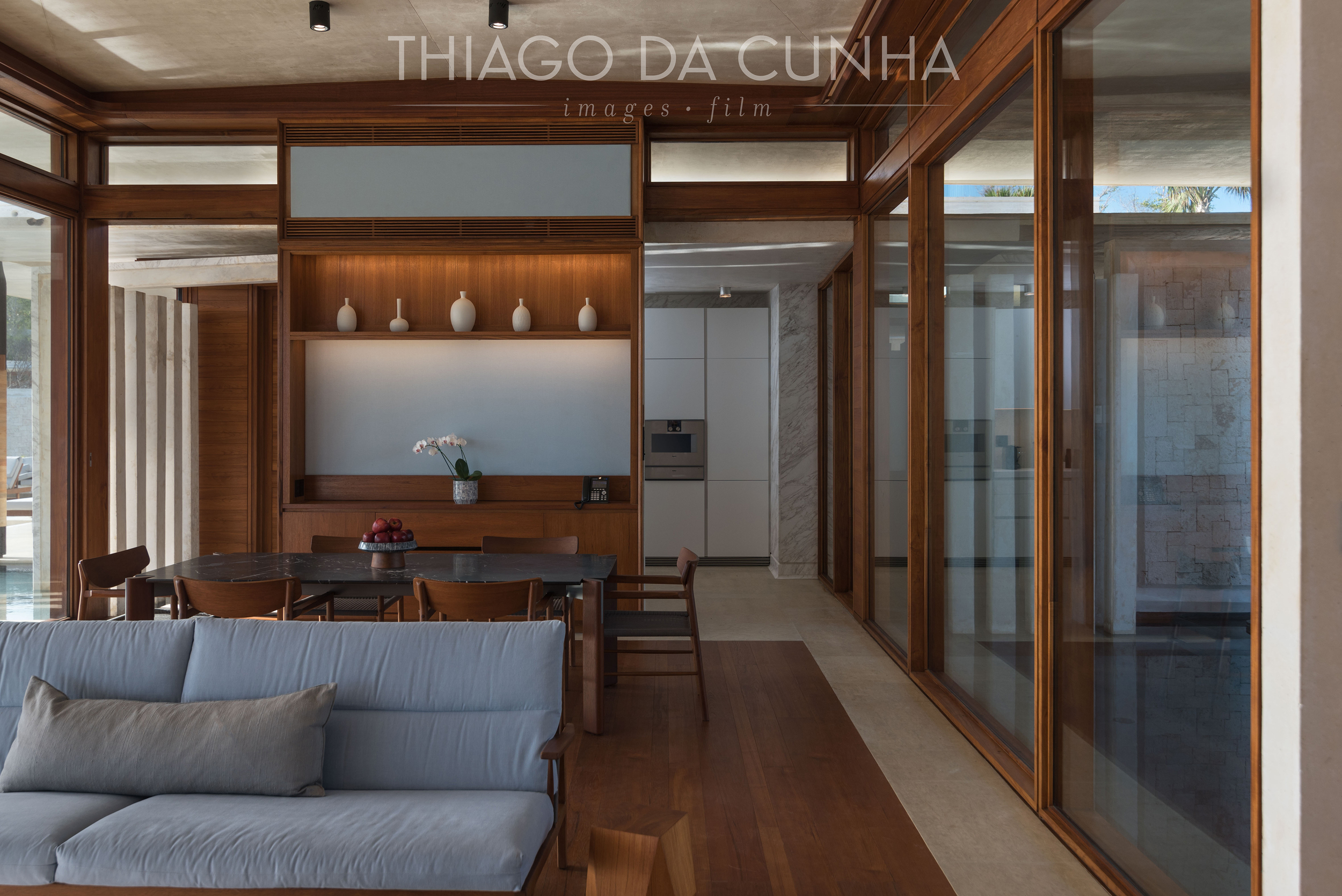 A detailed shot of the living room, dinning room and the kitchen. Again, wood and water is present as well as the large transparent glass windows on both sides of the villa.  http://thiagodacunhaphotography.com/