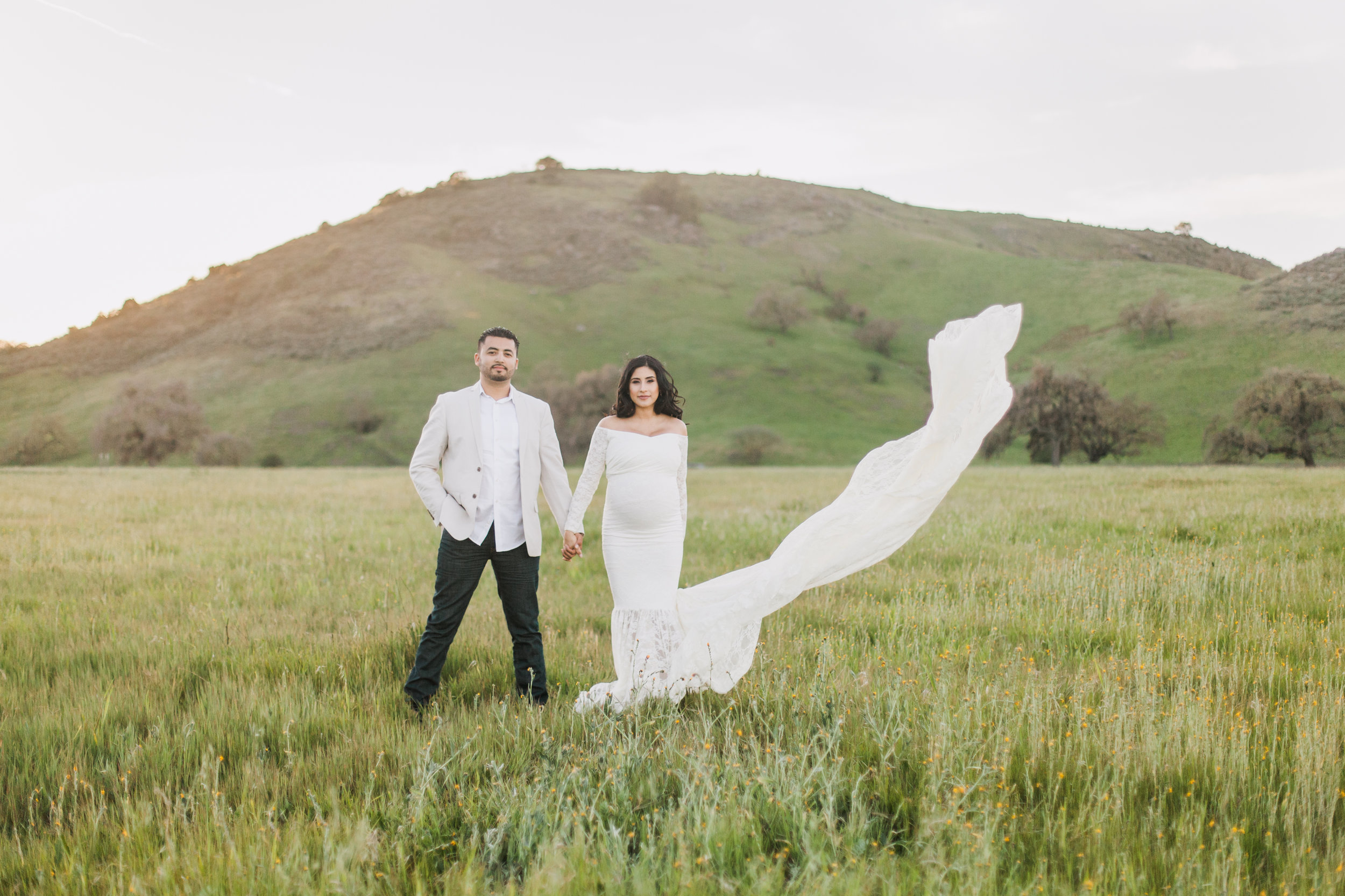 Couple standing in a field wearing during maternity session in San Jose, California.