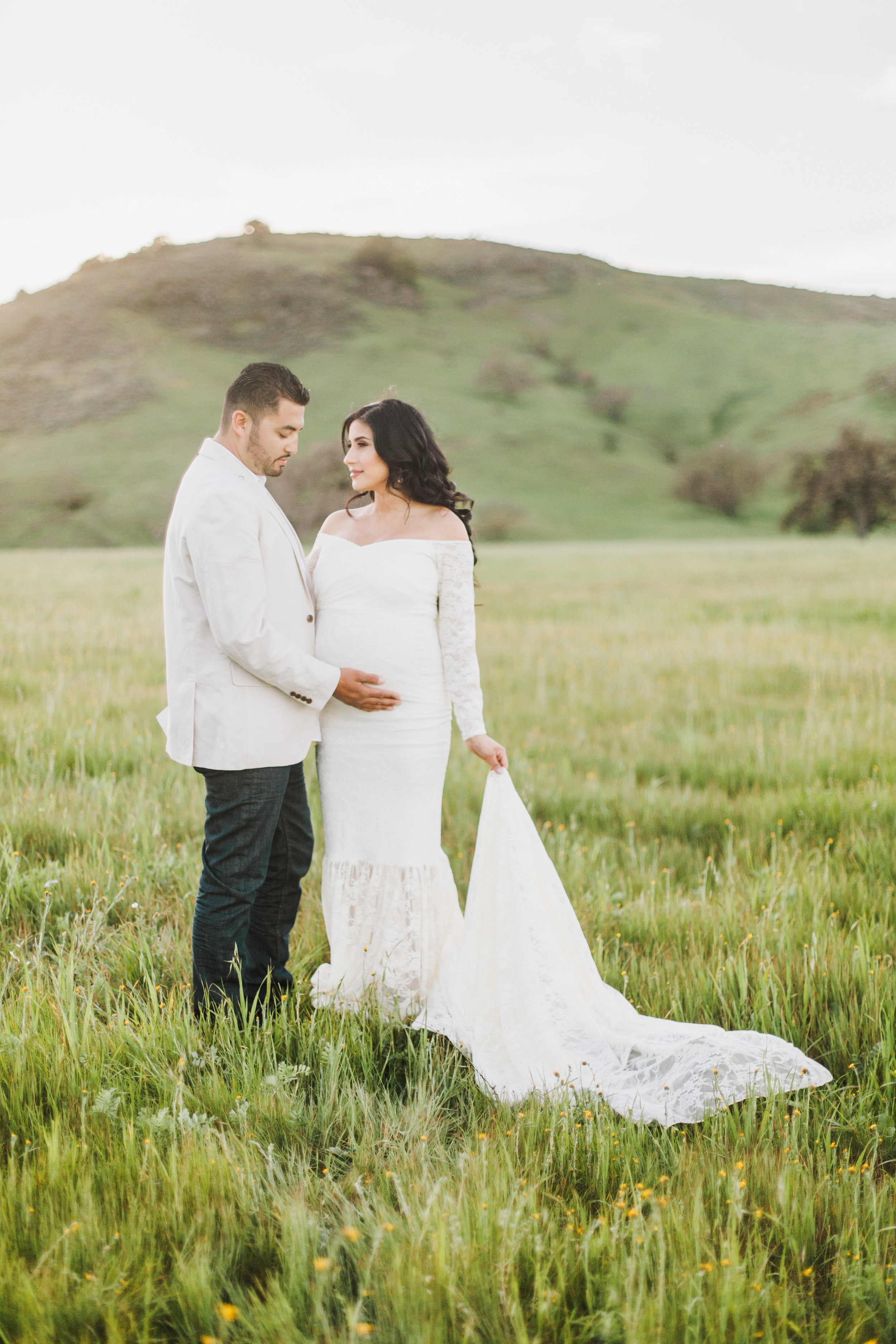 Couple standing in a grass field during maternity session in San Jose, California.