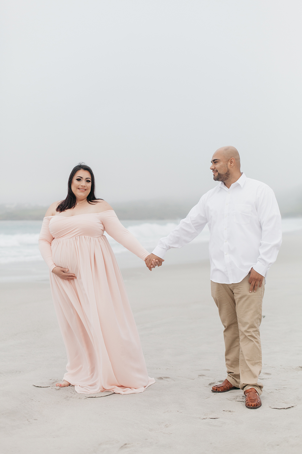 Husband and wife holding hands during their maternity photo session in Carmel-by-the-sea.