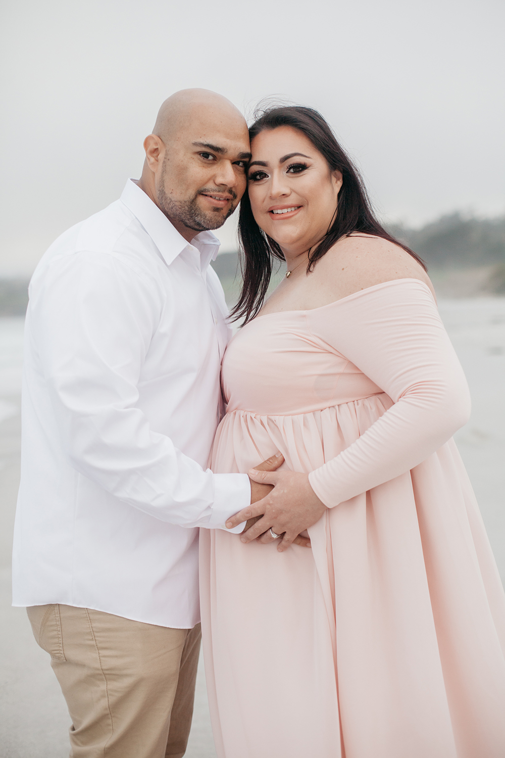 Husband and wife at the beach during their maternity photo session in Carmel-by-the-sea.