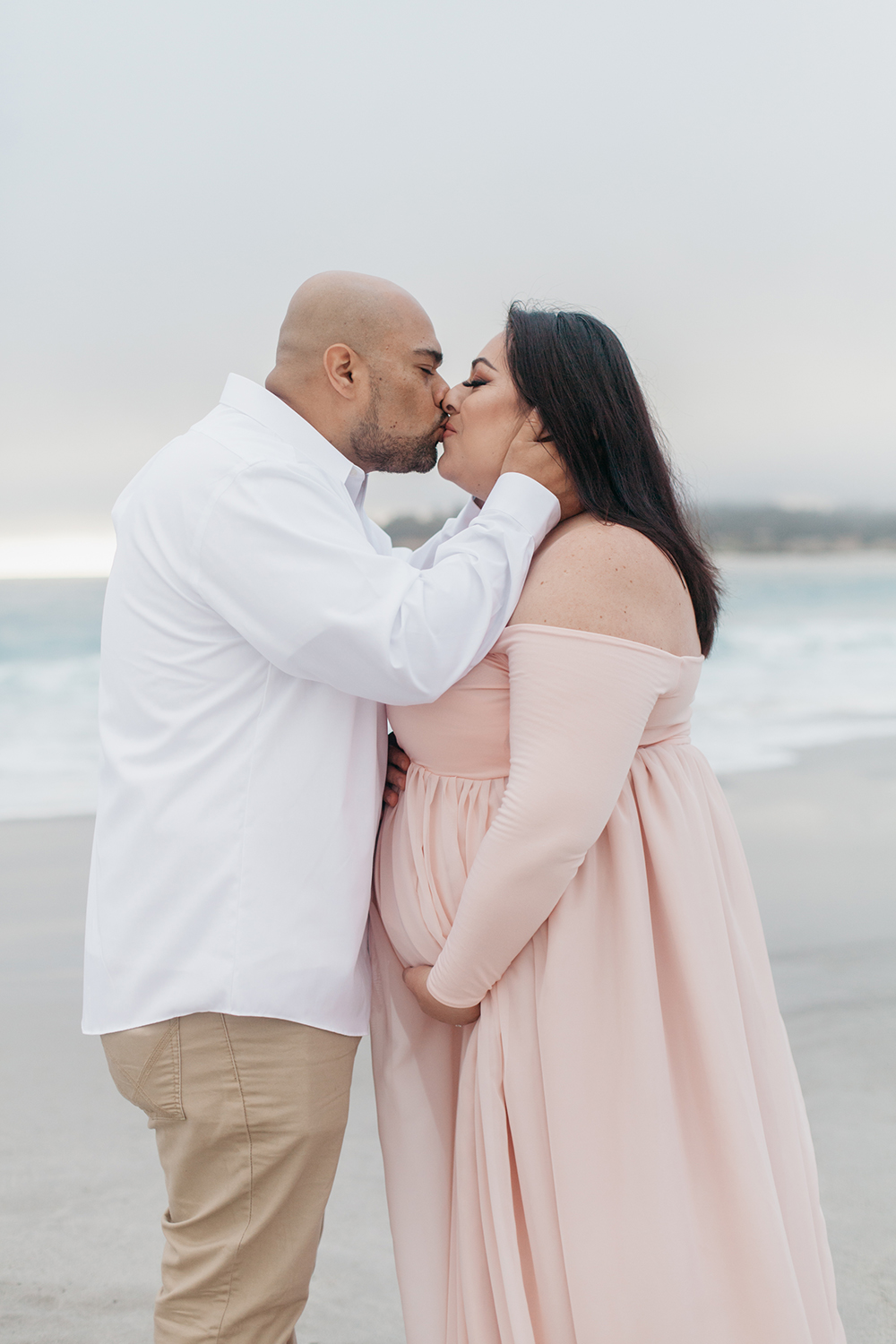 Husband and wife kissing during their maternity photos in Carmel-by-the-sea.
