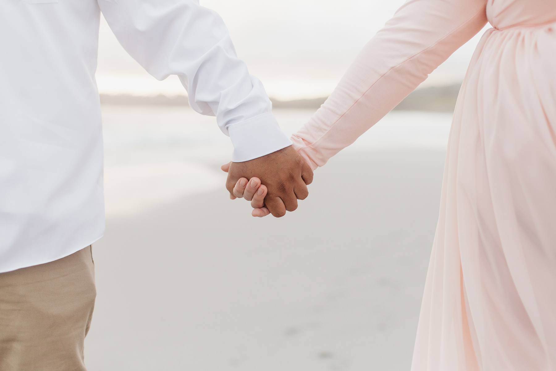 Couple holding hands while walking on the beach in Carmel.