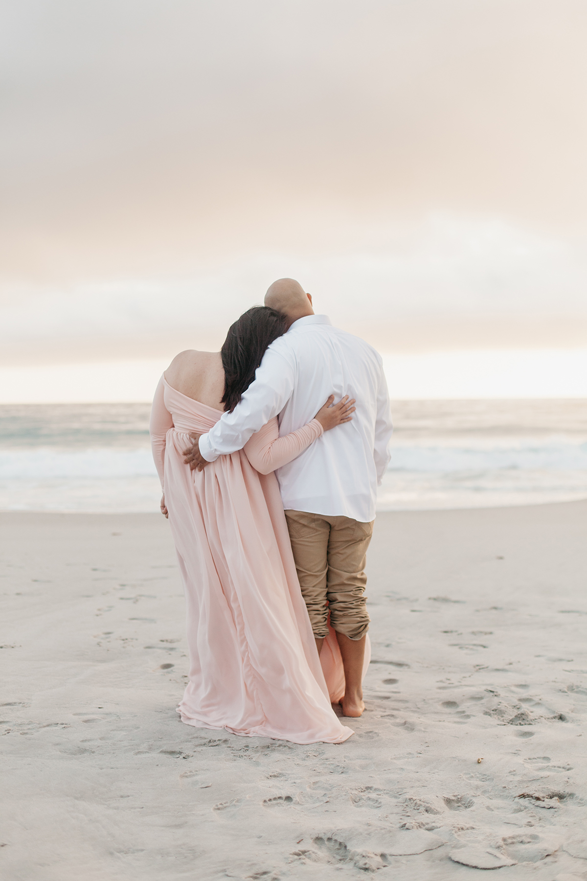 Couple holding eachtoher while staring away at the ocean.