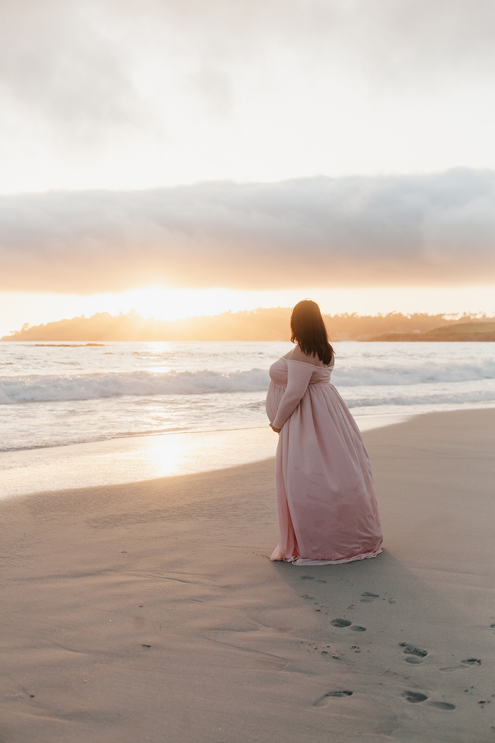 Pregnant woman in a pink dress standing on the beach looking away at the sunset.