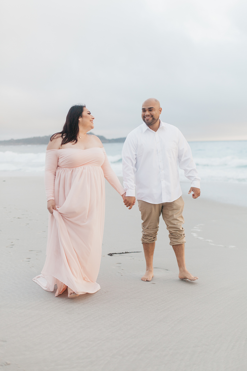 Couple walking along Carmel beach during their maternity photo session.