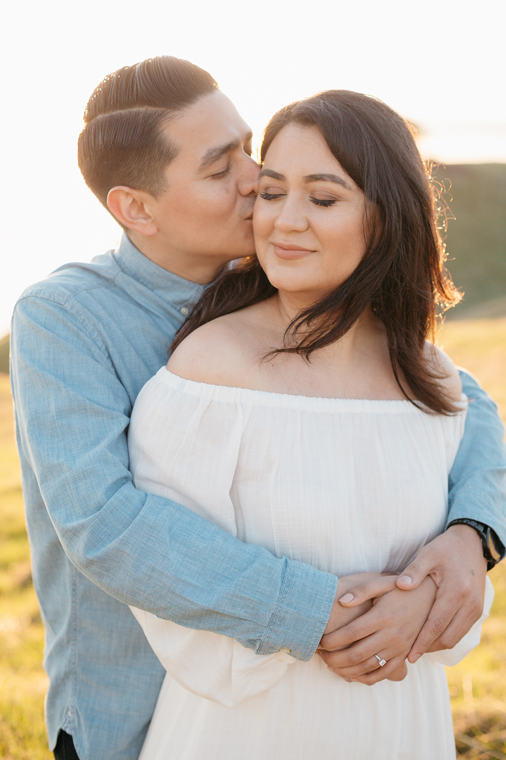 Portrait of couple kissing during their sunset engagement session in Mount Tamalpais in Marin, California.