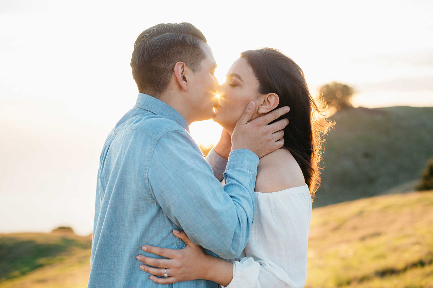 Romantic portrait of couple kissing during their sunset engagement session in Mount Tamalpais in Marin, California.