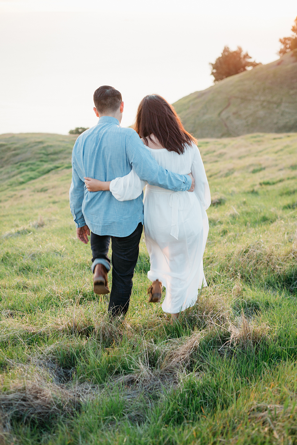 Couple walking together on a grass rolling hill during their engagement session in Mount Tamalpais in Marin, California.