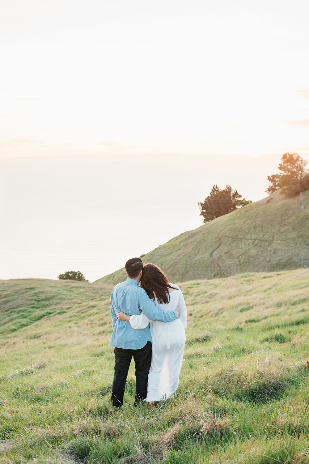 Couple staring at the sunset during their engagement session in Mount Tamalpais in Marin, California.