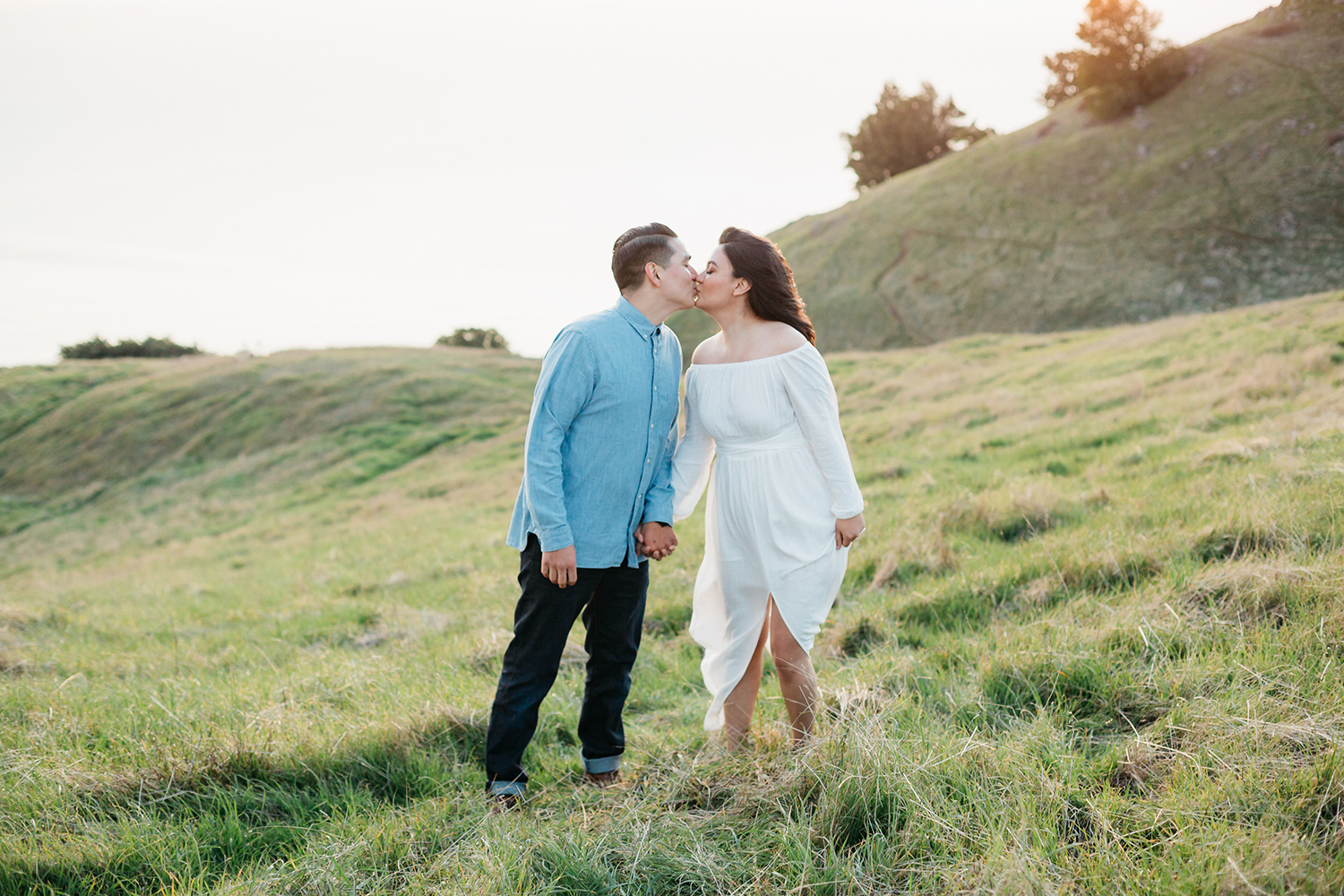 Couple kissing in a grass rolling hill during their engagement session in Mount Tamalpais in Marin, California.