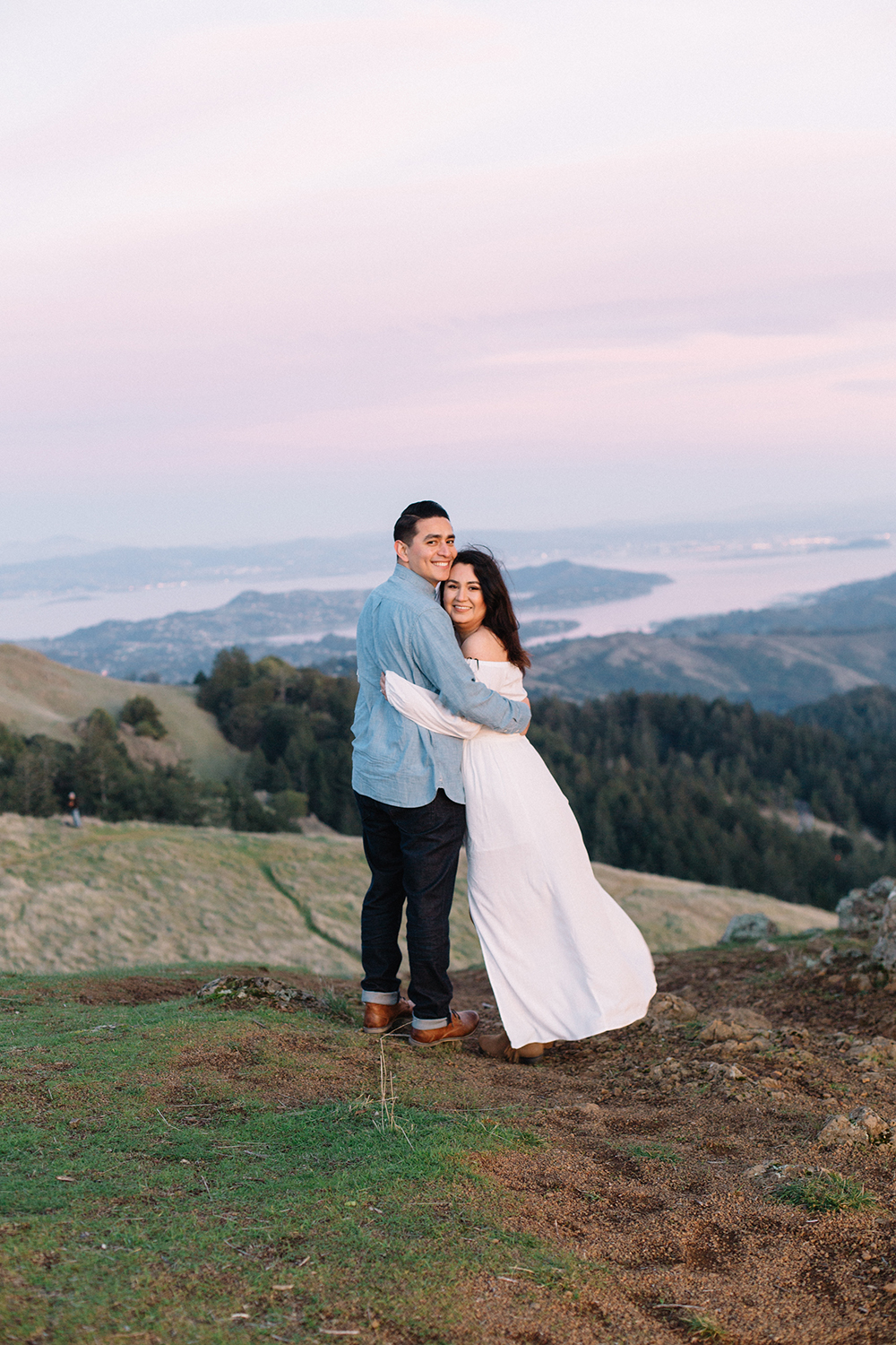 Portrait of a couple with a view of the San Francisco Bay Area in the background during their engagement session in Mount Tamalpais in Marin, California.