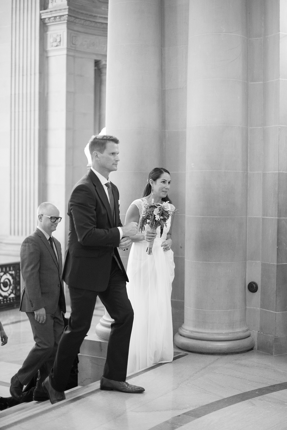 Bride and groom walking towards their wedding ceremony in San Francisco City Hall.