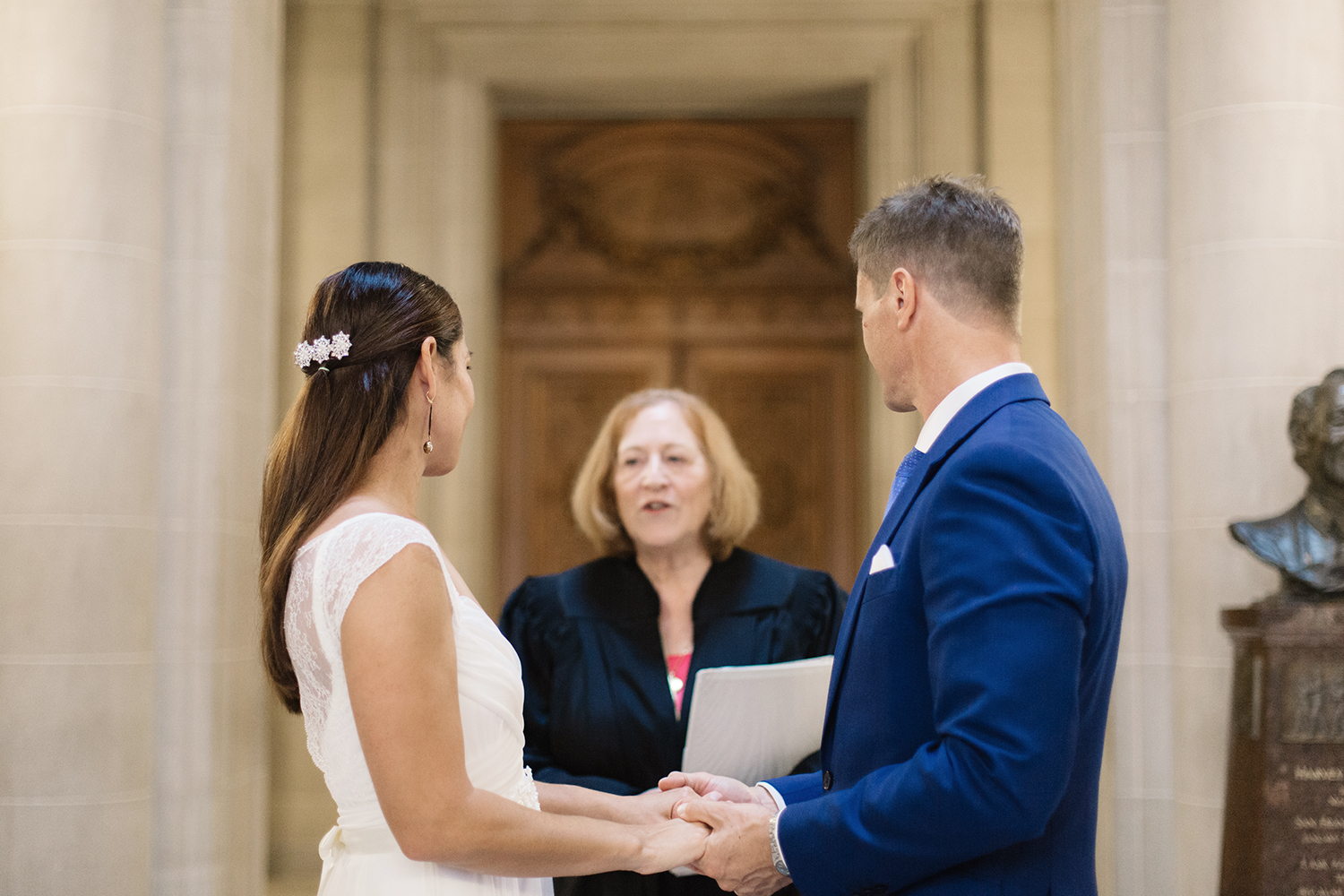 Bride and groom holding hands during their ceremony in San Francisco City Hall.