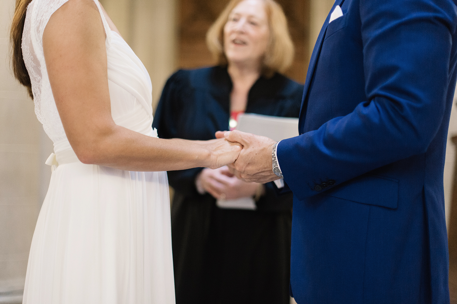 Bride and groom holding hands during their wedding ceremony in San Francisco City Hall.