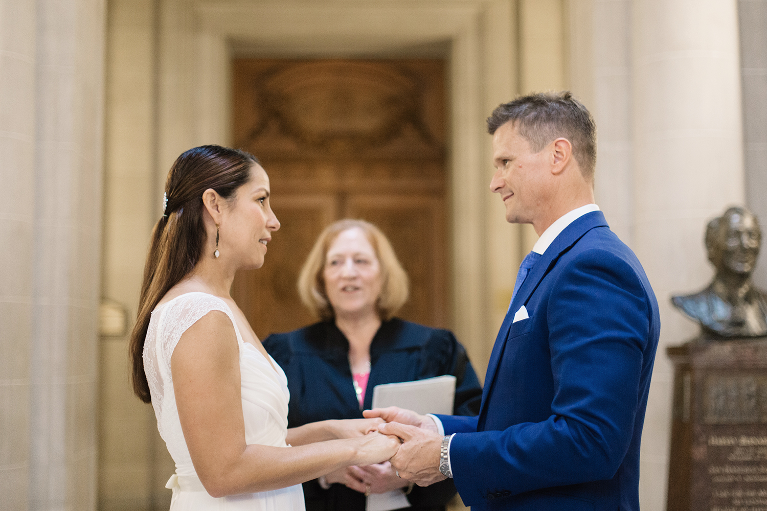 Bride and groom exchanging vows during their wedding in San Francisco City Hall.