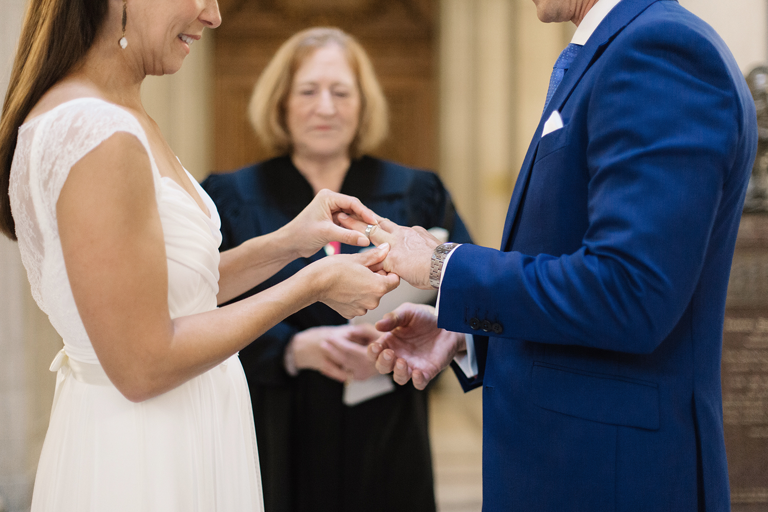 Bride and groom exchanging rings during their wedding in San Francisco City Hall.