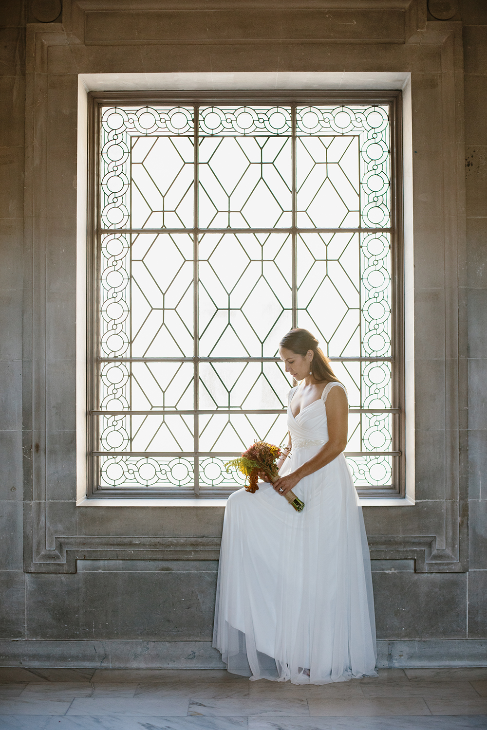 Bride sitting by window after her wedding in San Francisco City Hall.