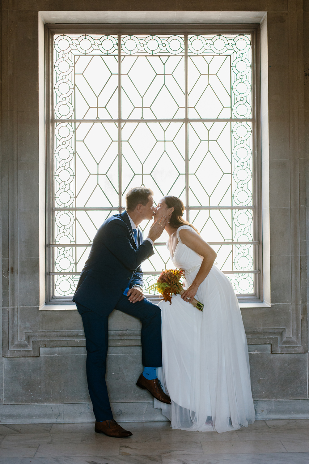 Bride and groom kissing by window after eloping in San Francisco City Hall