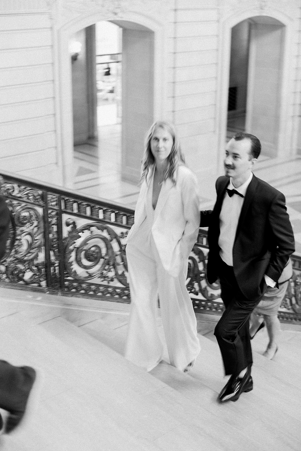 Bride and groom walking up stairs during their wedding in San Francisco City Hall.