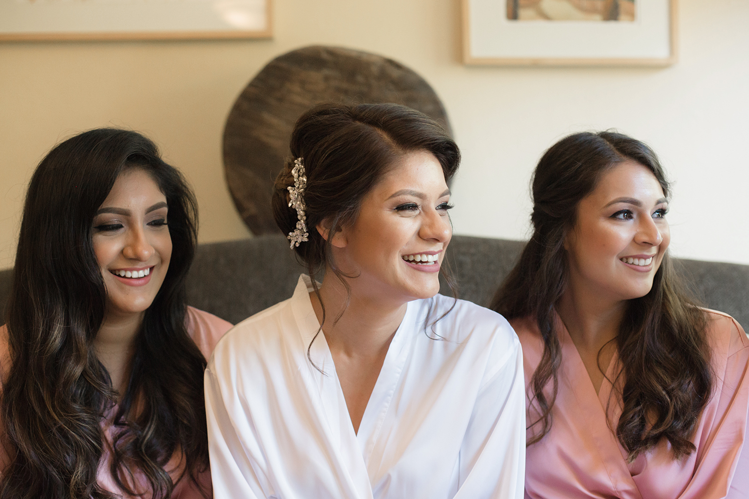 A bride laughing with her bridesmaids before putting her wedding dress on.