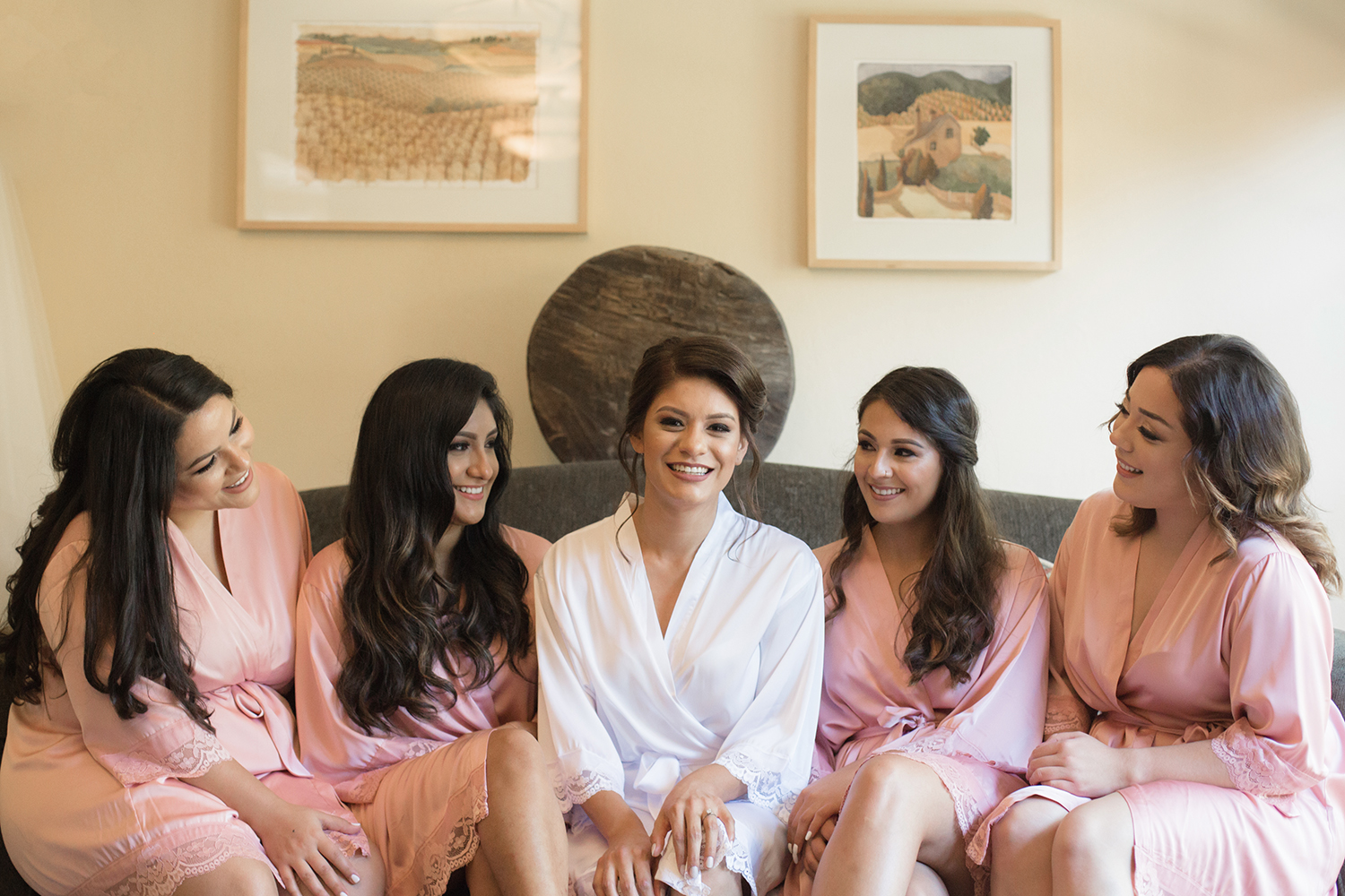 A modern bride sitting next to her bridesmaids all in the robes.