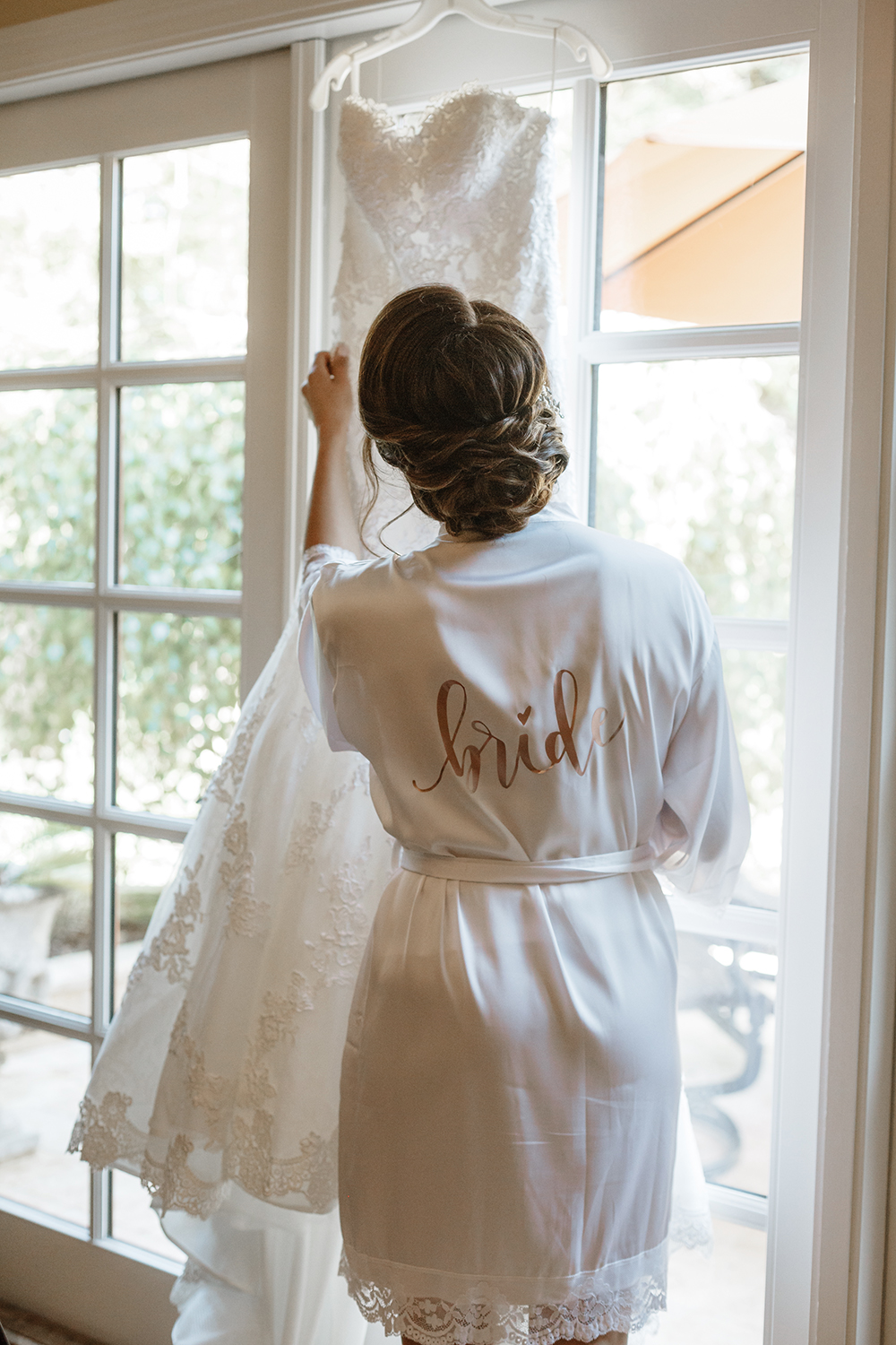 Bride looking at her wedding dress hanging by the door.